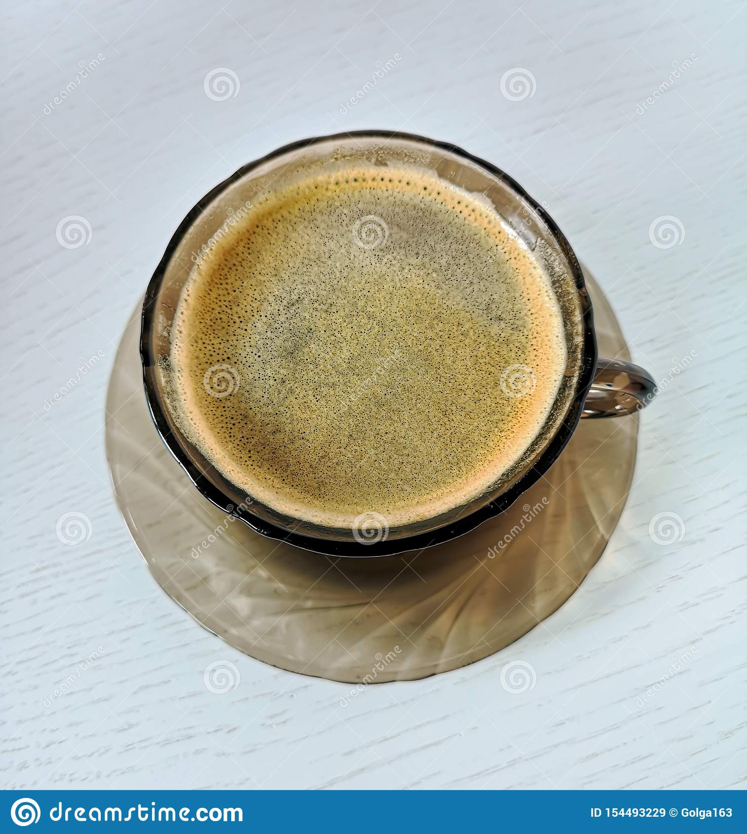 Saucer and cup of tempered brown glass with black coffee stand on a white wooden table