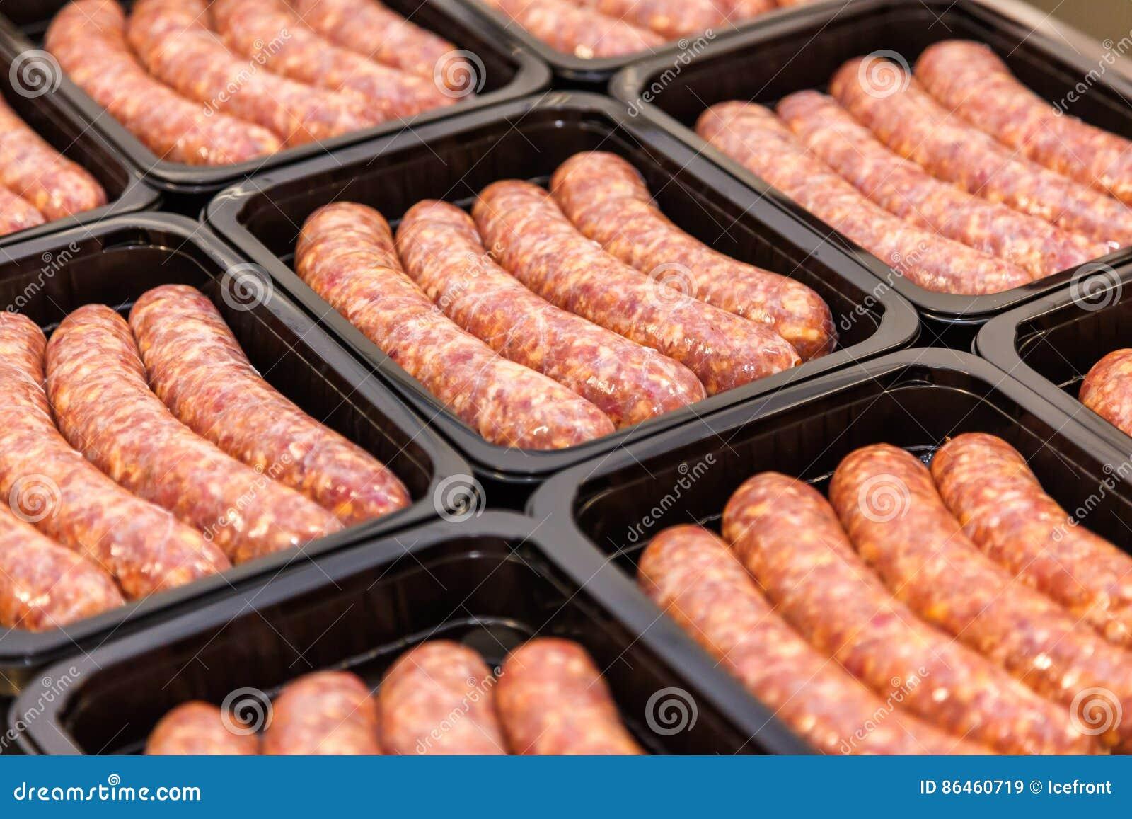 Saucisses de viande crue dans la caisse d emballage