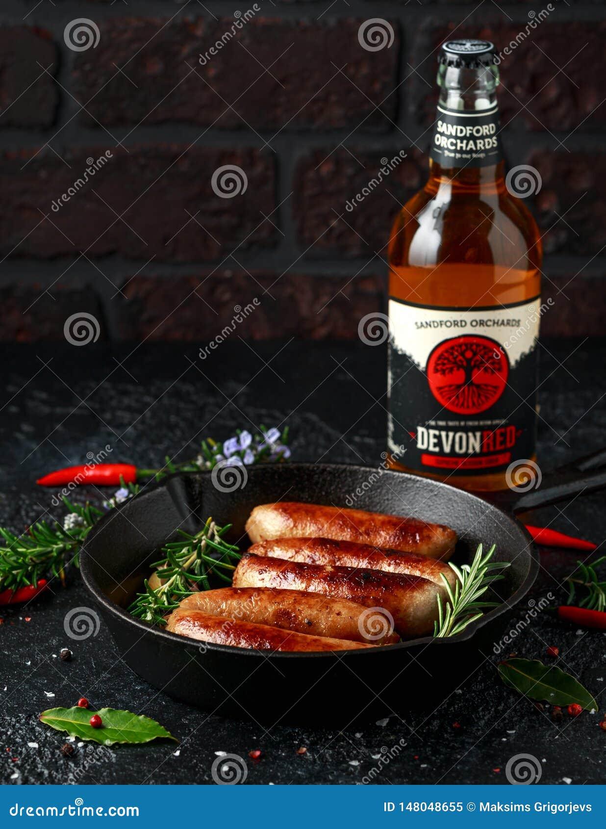 Saucisses fraîchement cuites de bouchers dans les peaux dans la poêle de fonte avec le cidre de pomme de vergers de Sanford, Devo