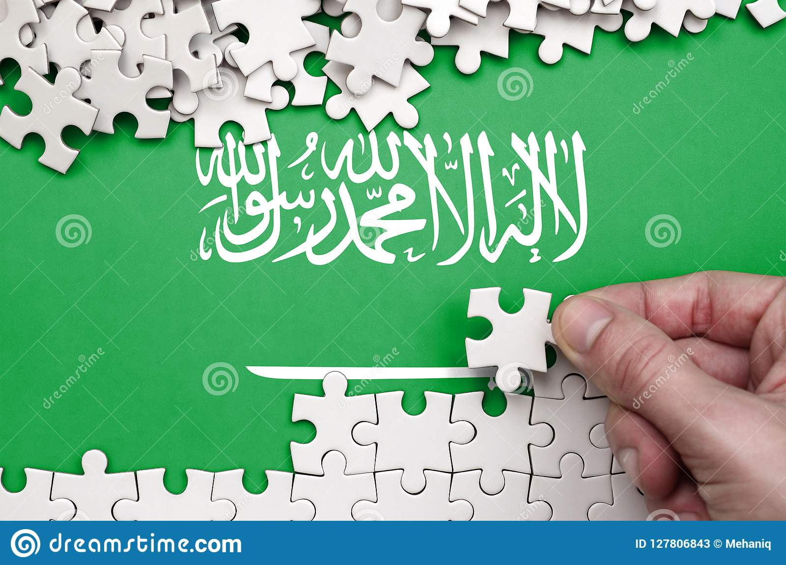 Saudi Arabia flag is depicted on a table on which the human hand folds a puzzle of white color