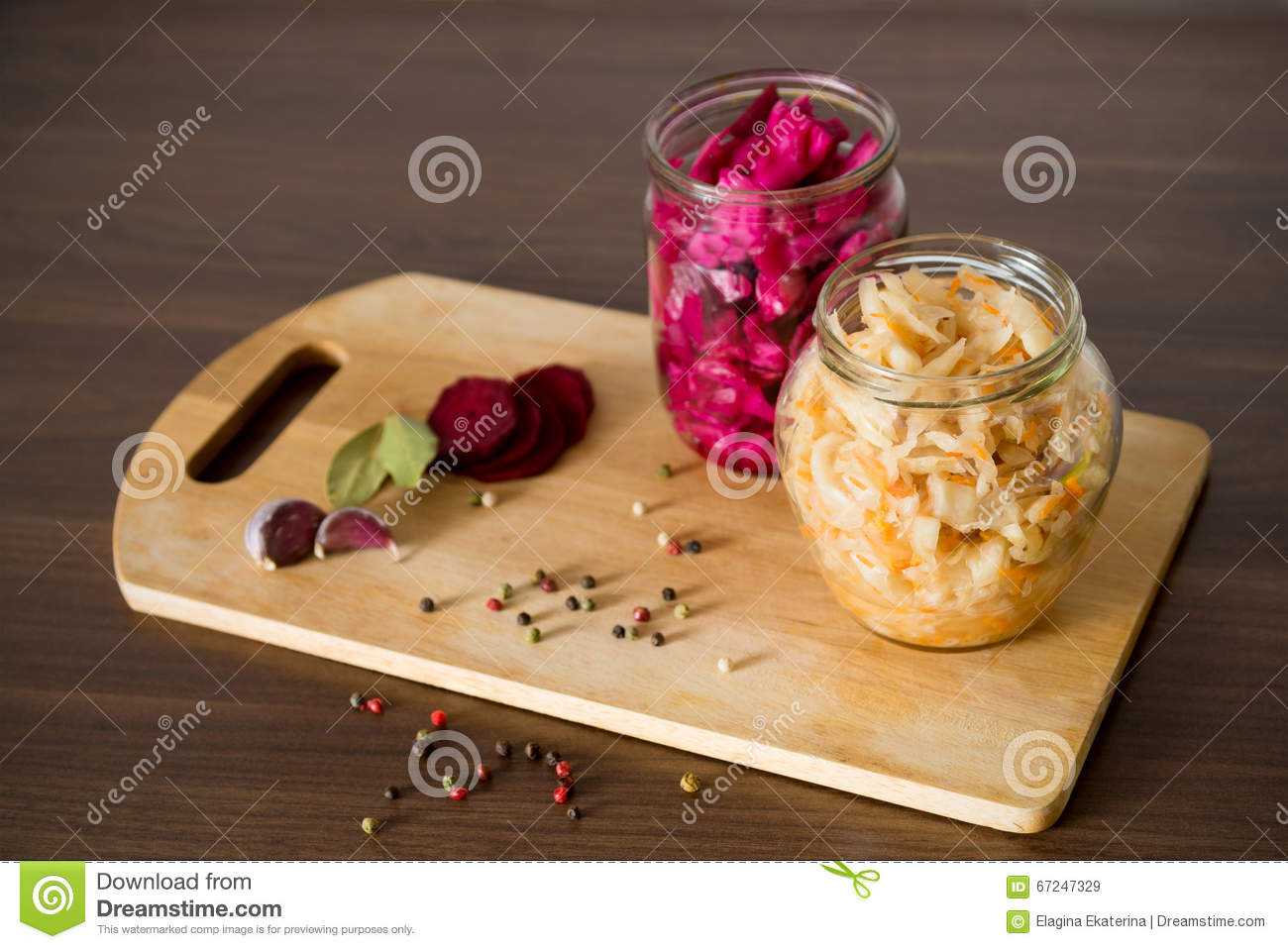Sauerkraut with beets and spices in a glass jar on wooden backgr