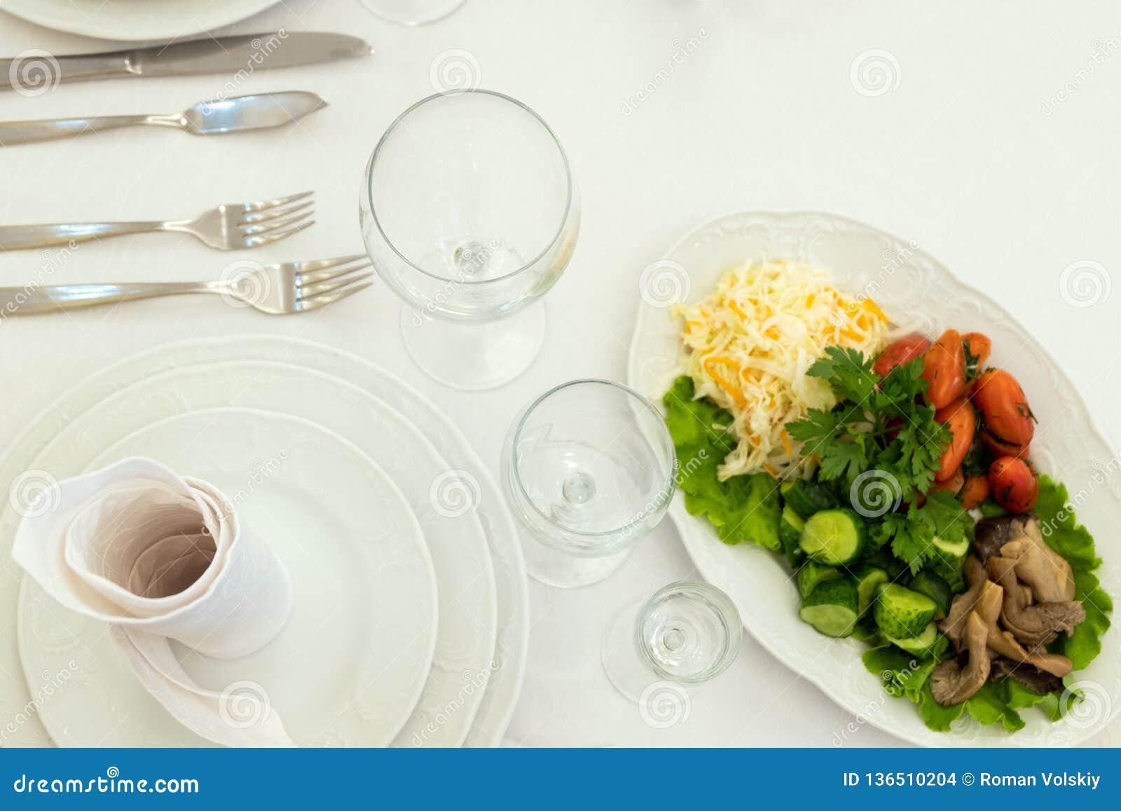 Sauerkraut, pieczarki, pomidory, ogórki, sałata Naczynie od menu z zimnymi przekąskami Talerze, pieluchy, rozwidlenia, noże, szkł