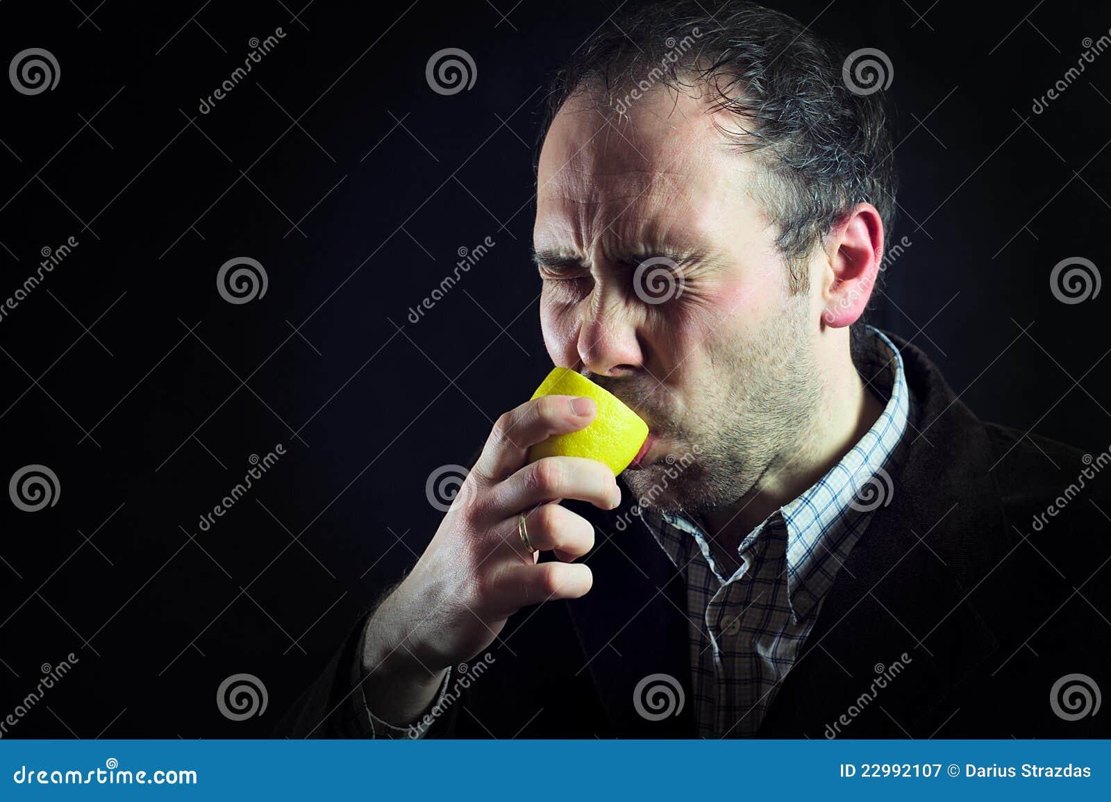 Saurer Zitroneausdruck, der Mann im Schwarzen saugt
