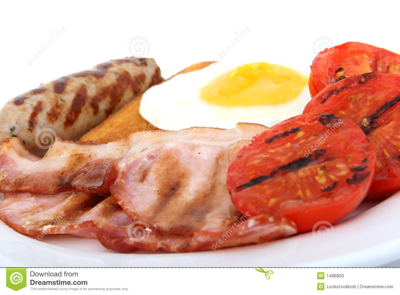 Sausage, bacon tomato and egg breakfast with toast and hash browns ...