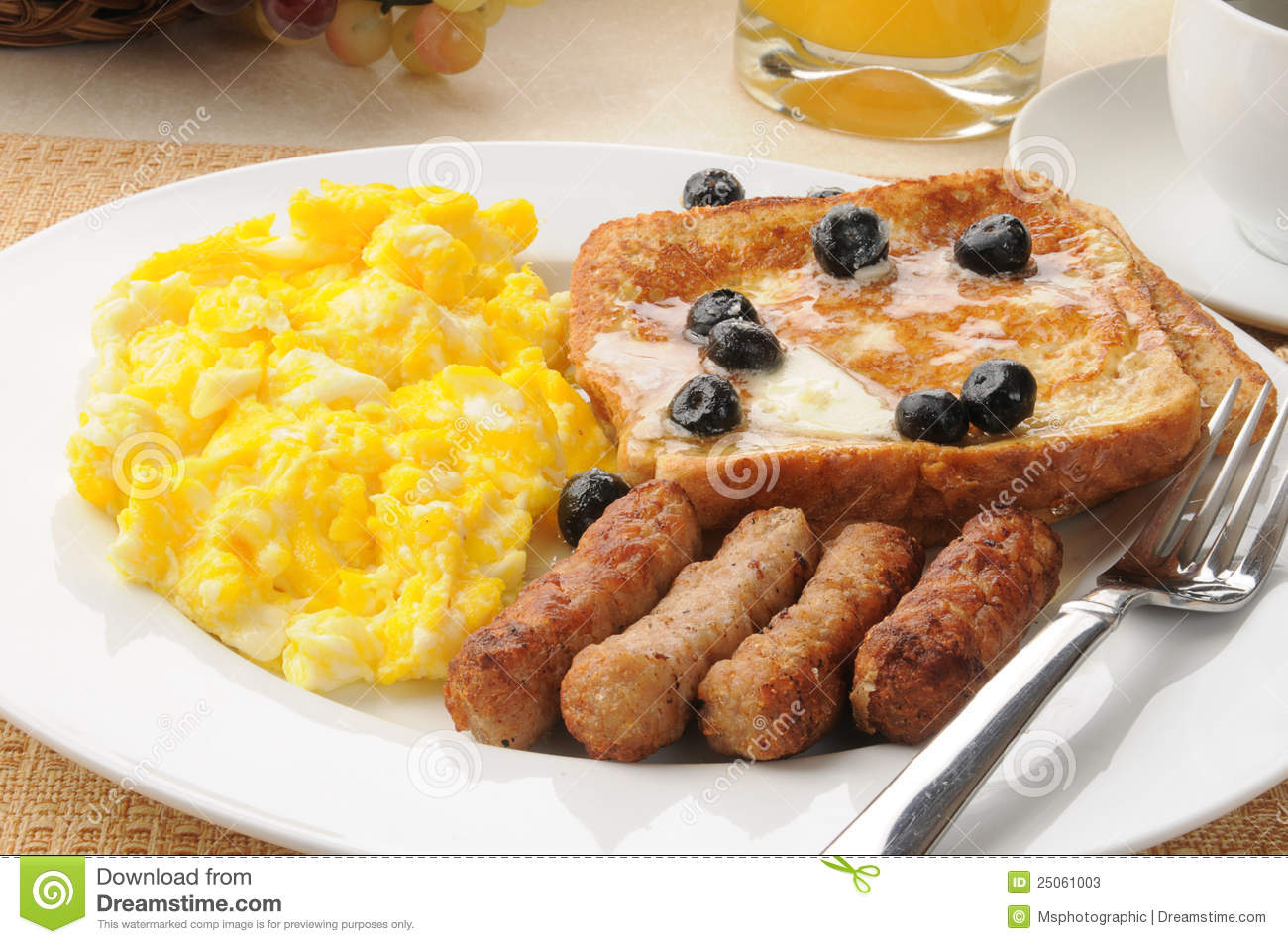 sausage and egg breakfast with french toast and blueberries.