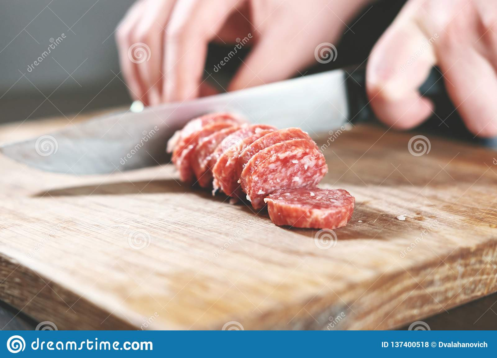 Sausage, knife, hands of woman, thick pieces, wooden plank, knife in female hands, woman cuts the sausage