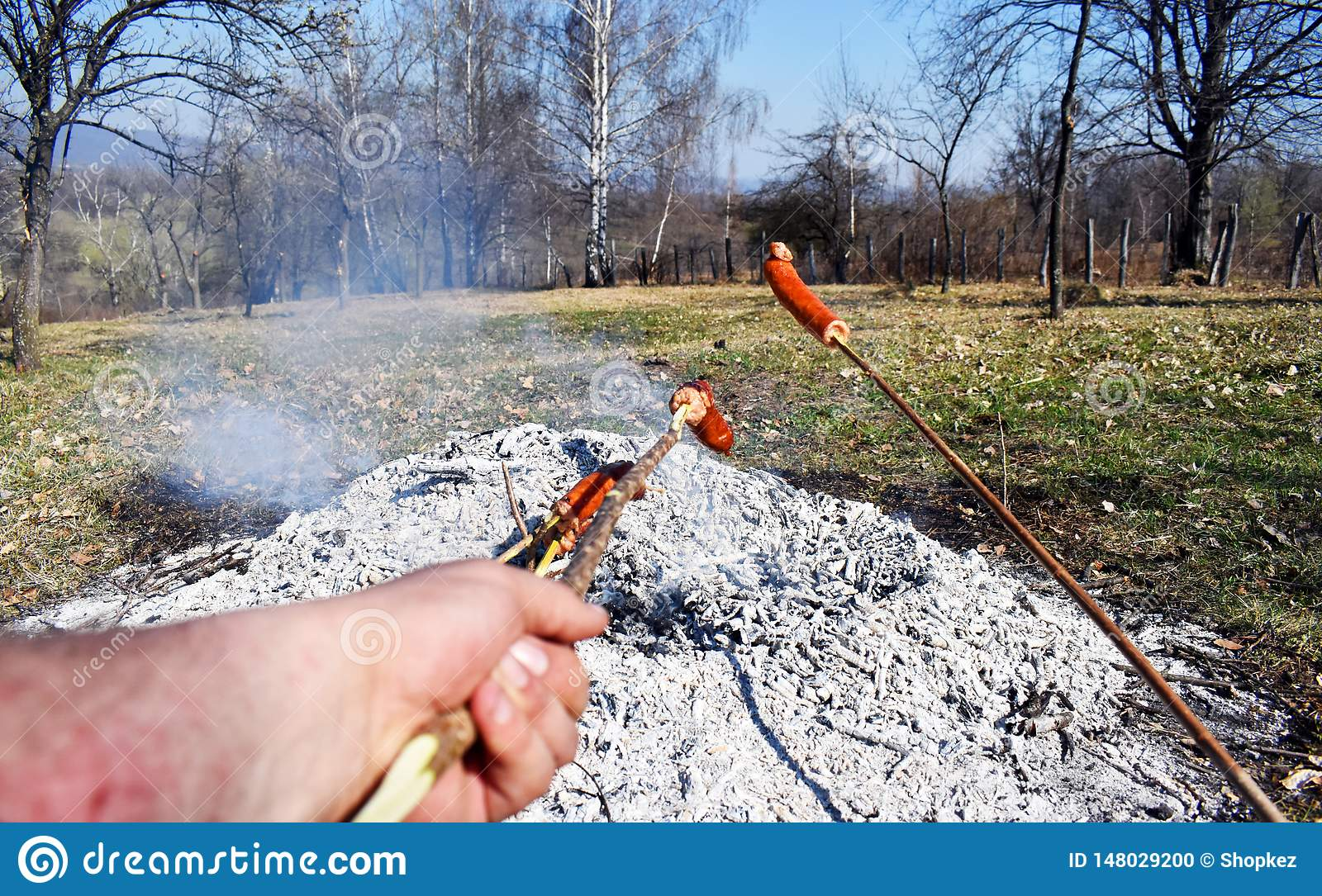 Sausage skewers are heated by grilling on a special slow fire for a long time to eat as a family breakfast on holiday and prepared