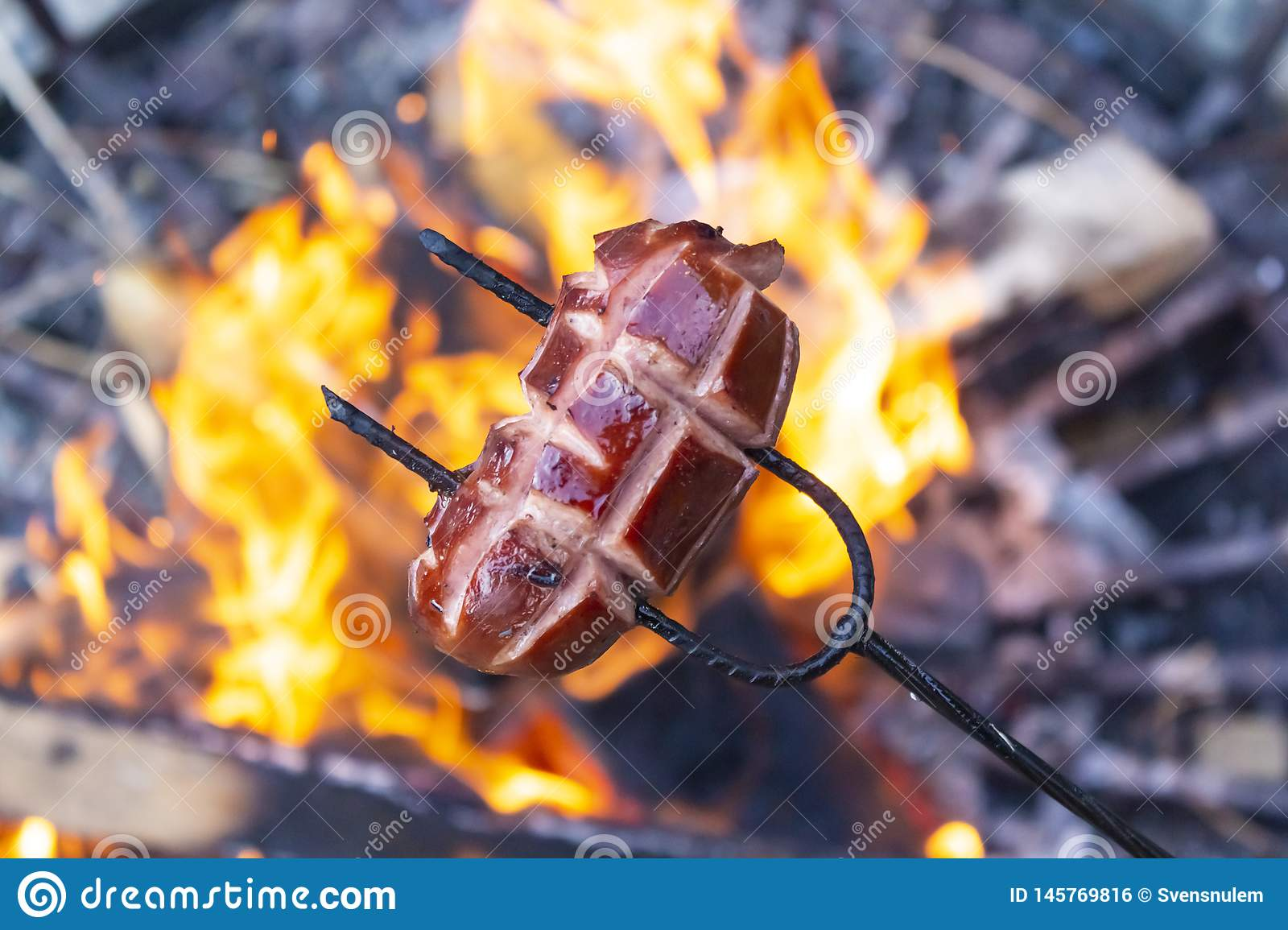 Sausages baking over camp fire. Party with friends