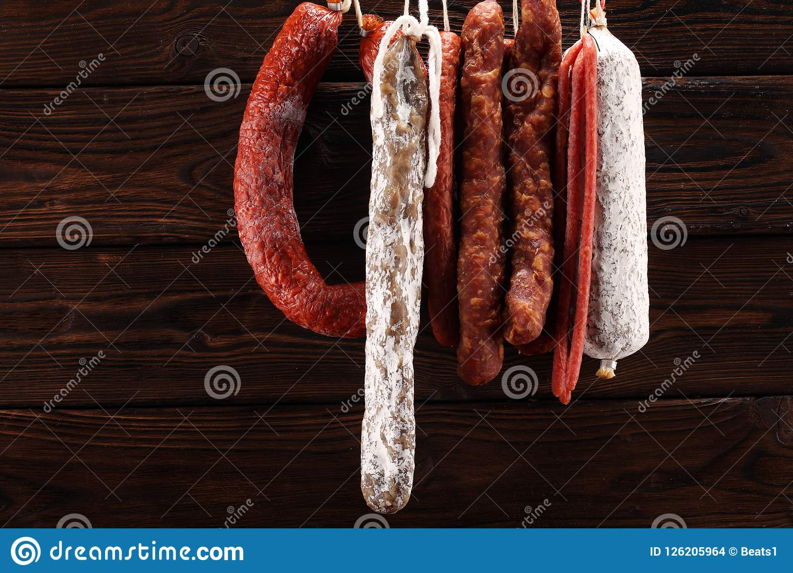 sausages hang from a rack at market. Country dark style. Traditional food. Smoked sausages meat hanging