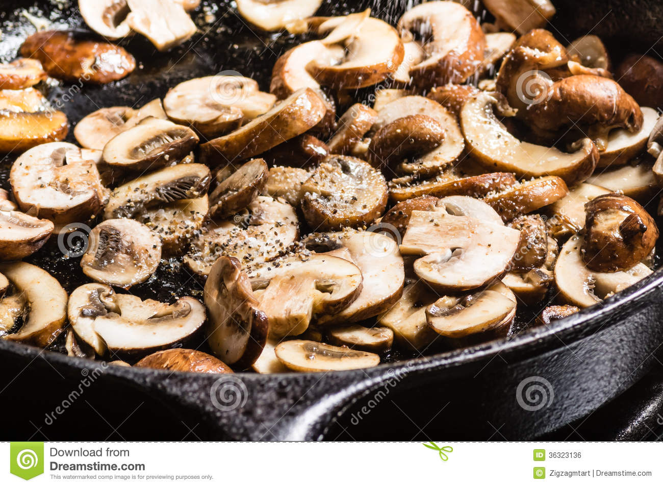Sauteing sliced mushrooms in a cast iron skillet.