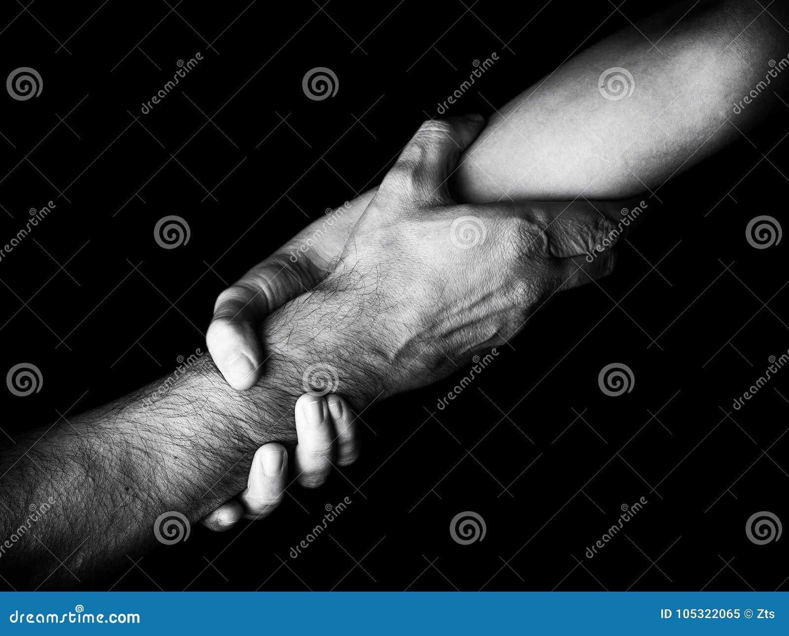 Sauveteur d économie de femme, et d aide en se tenant ou ronchonnant l avant-bras Main femelle et bras tirant vers le haut le mâl