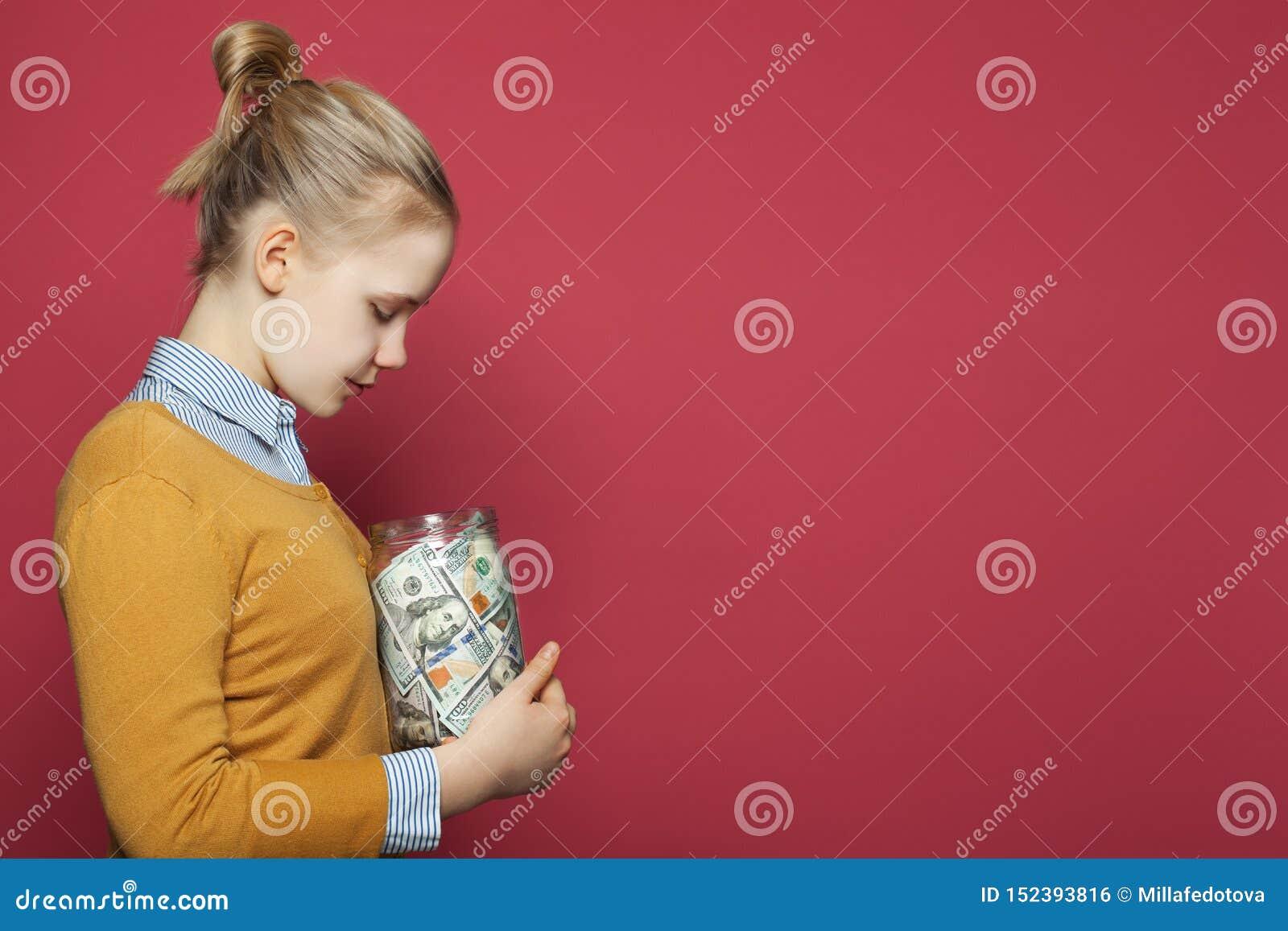 Saving money concept. Pretty young girl holding money cash