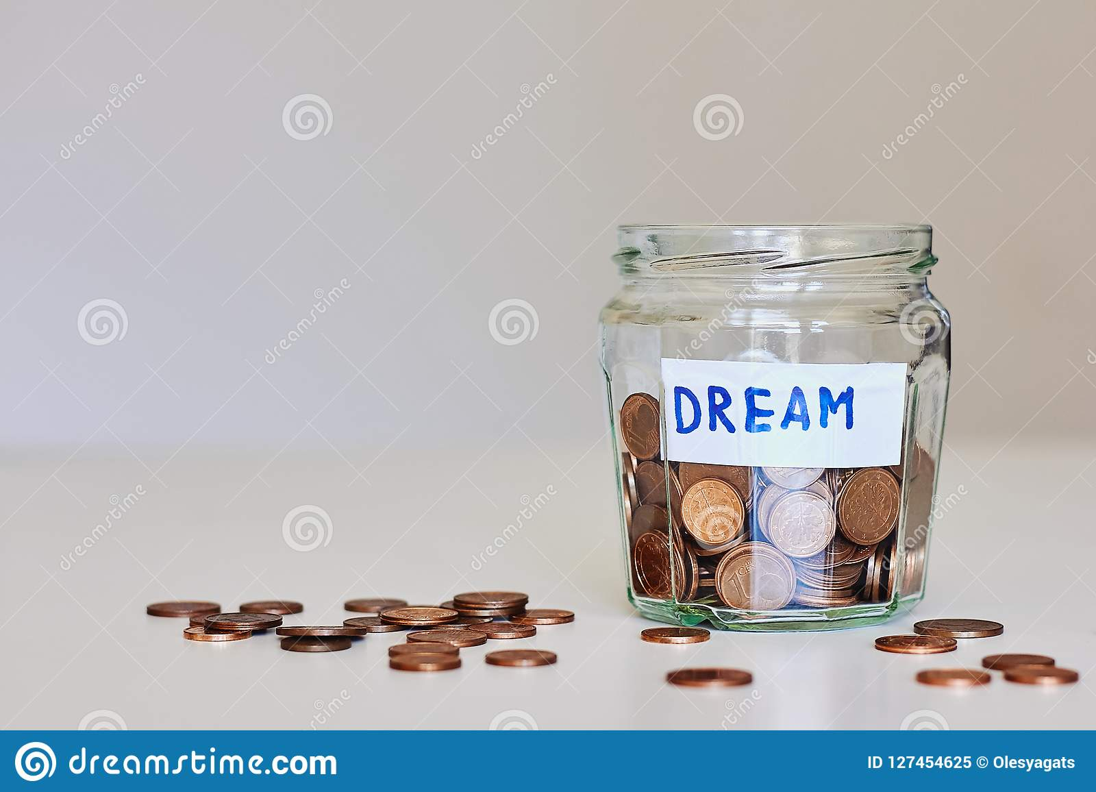 Saving money for dream concept. Glass jar full of coins and sign dream