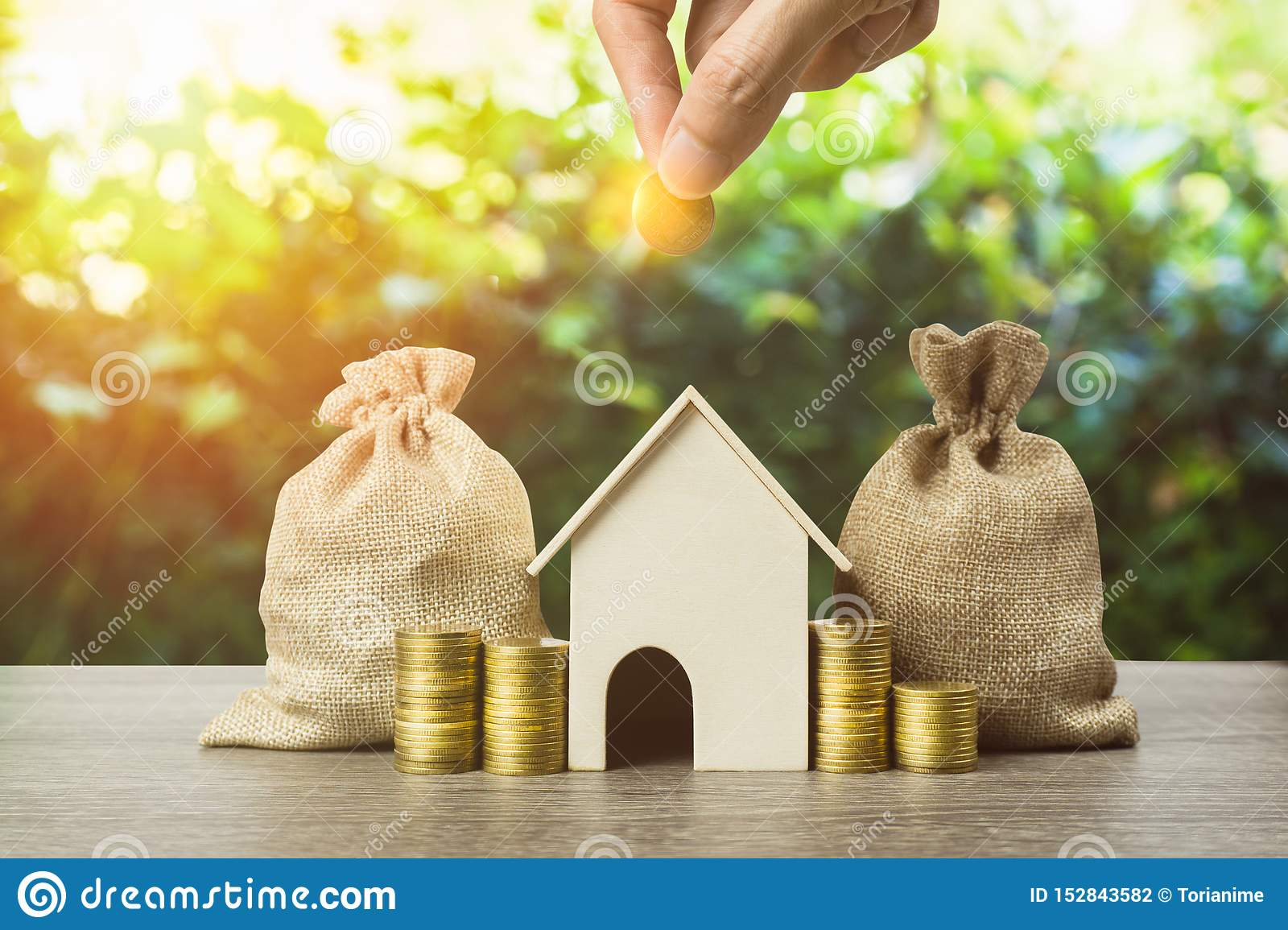 Saving money, home loan, mortgage, a property investment for future concept. A man hand putting money coin over small residence