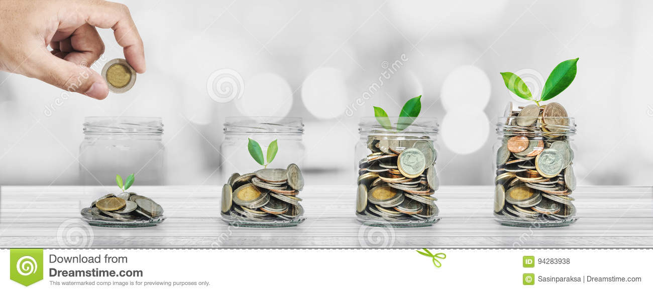 Saving money and investment concepts, Hand putting coin in glass bottles with plants glowing
