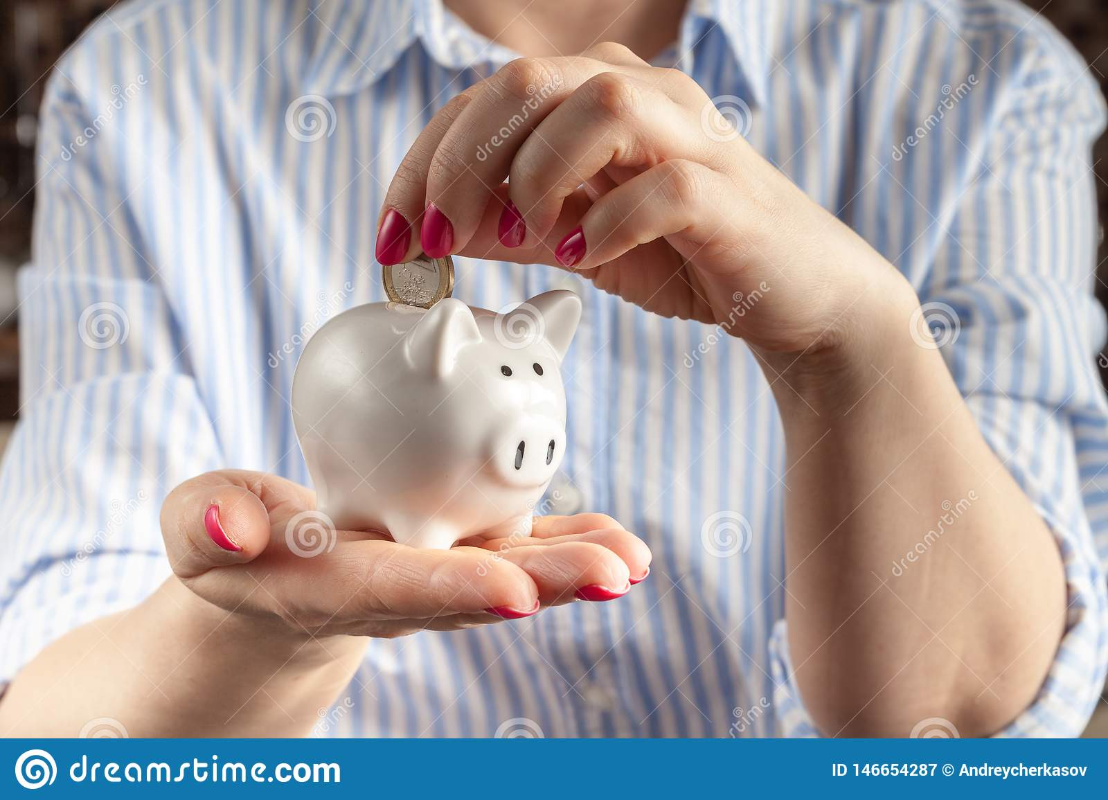 Savings concept,white piggy bank with human female hand inserting coin inside