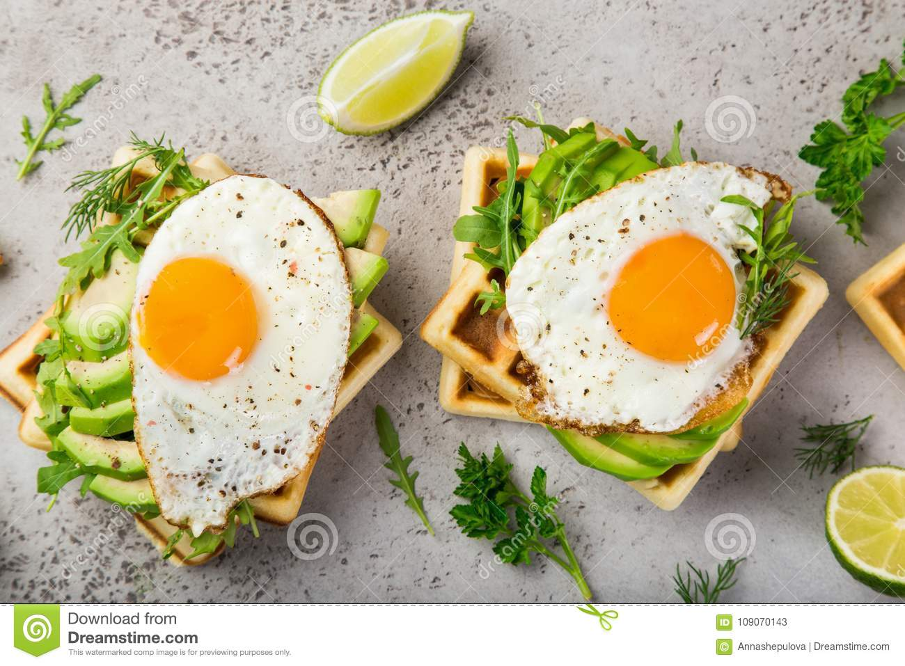Savory waffles with avocado, arugula and fried egg for breakfast