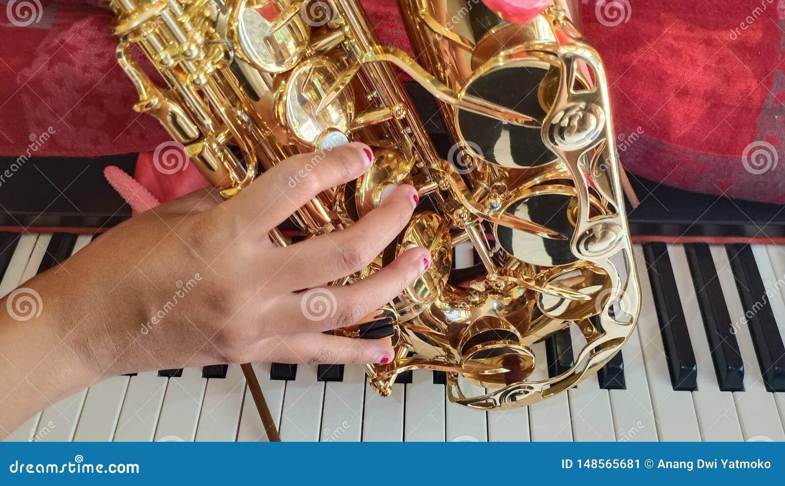 Saxofón, mano de la muchacha y el piano