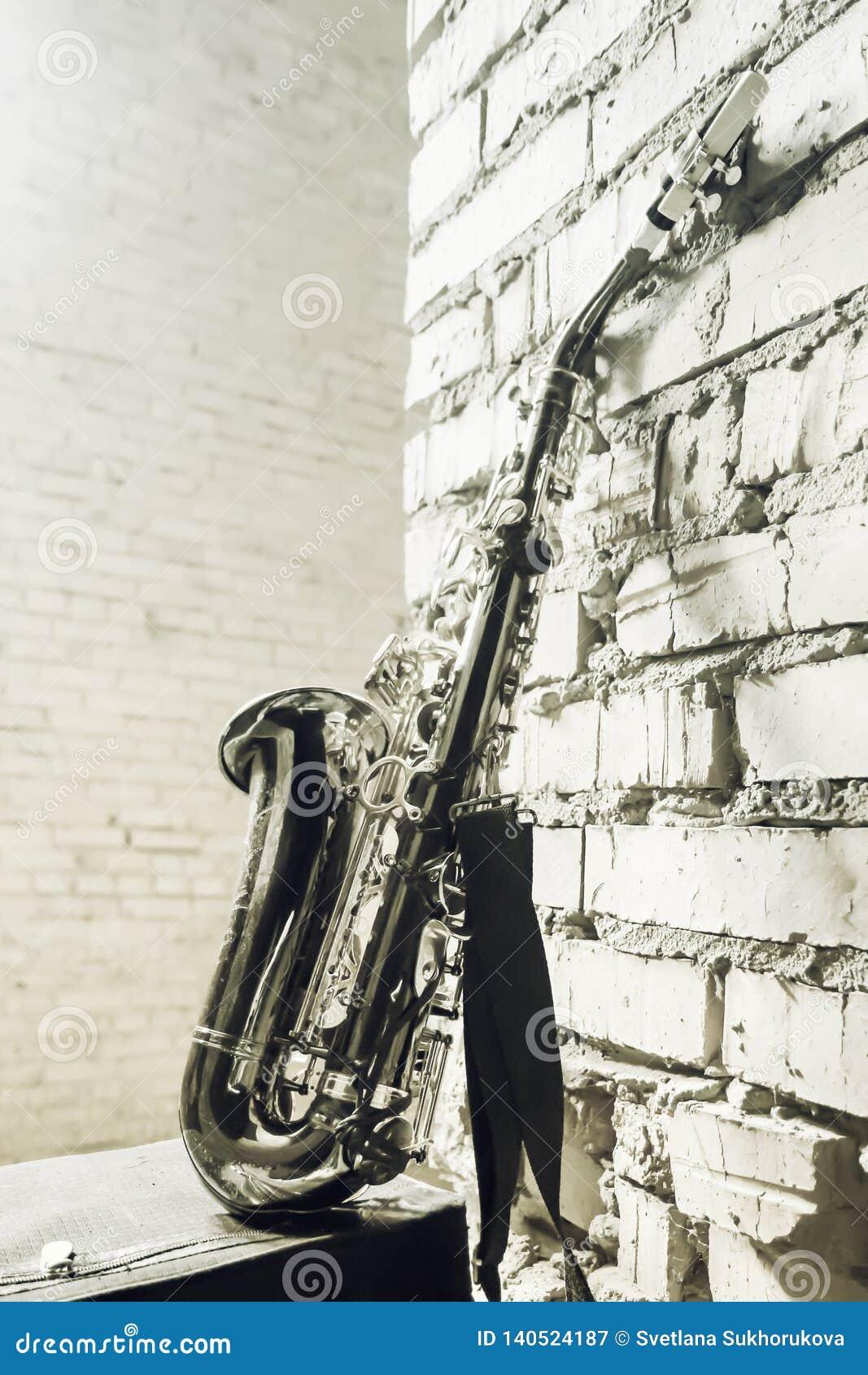 Saxofon på bakgrunden för tegelstenvägg - tappning tonad bild