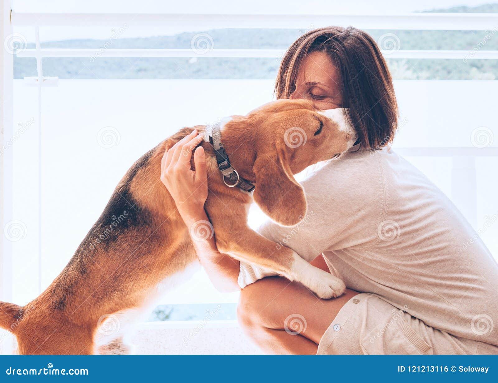 Scène à la maison tendre avec la propriétaire de femme et son chien de briquet