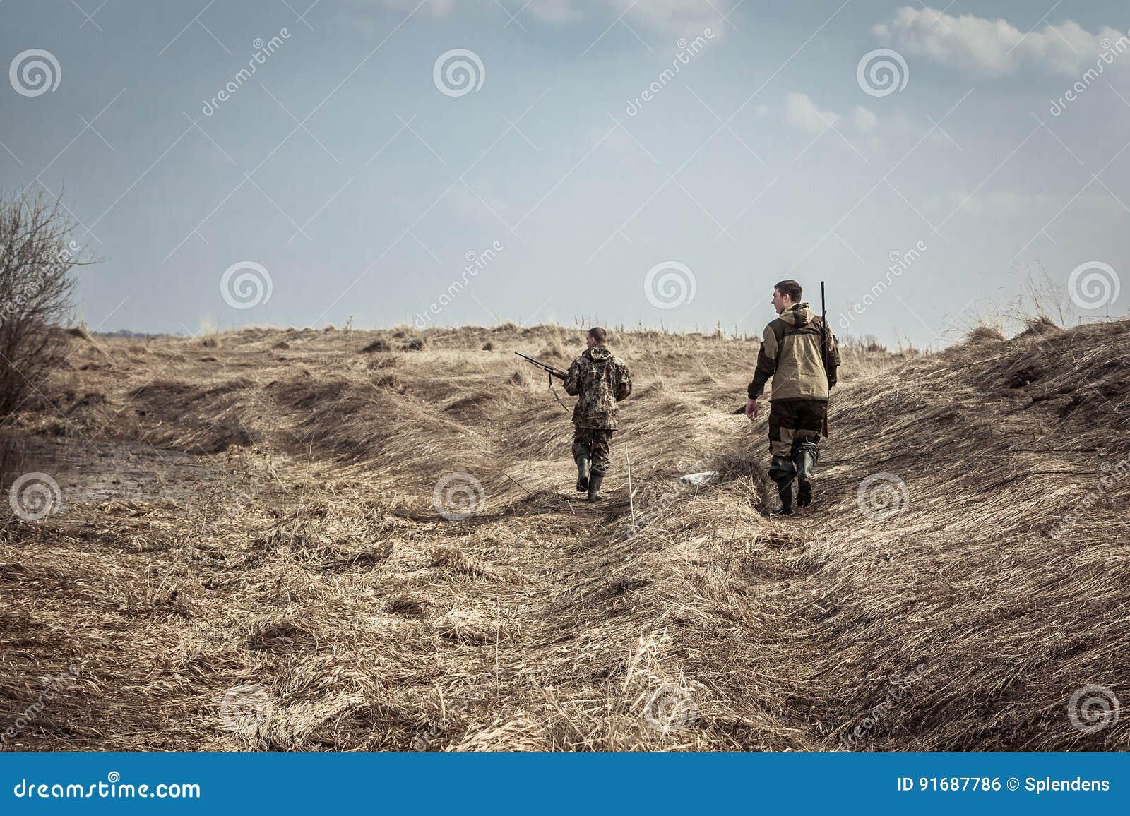 Scène de chasse avec des chasseurs des hommes avec des fusils de chasse explorant la zone rurale pendant la saison de chasse