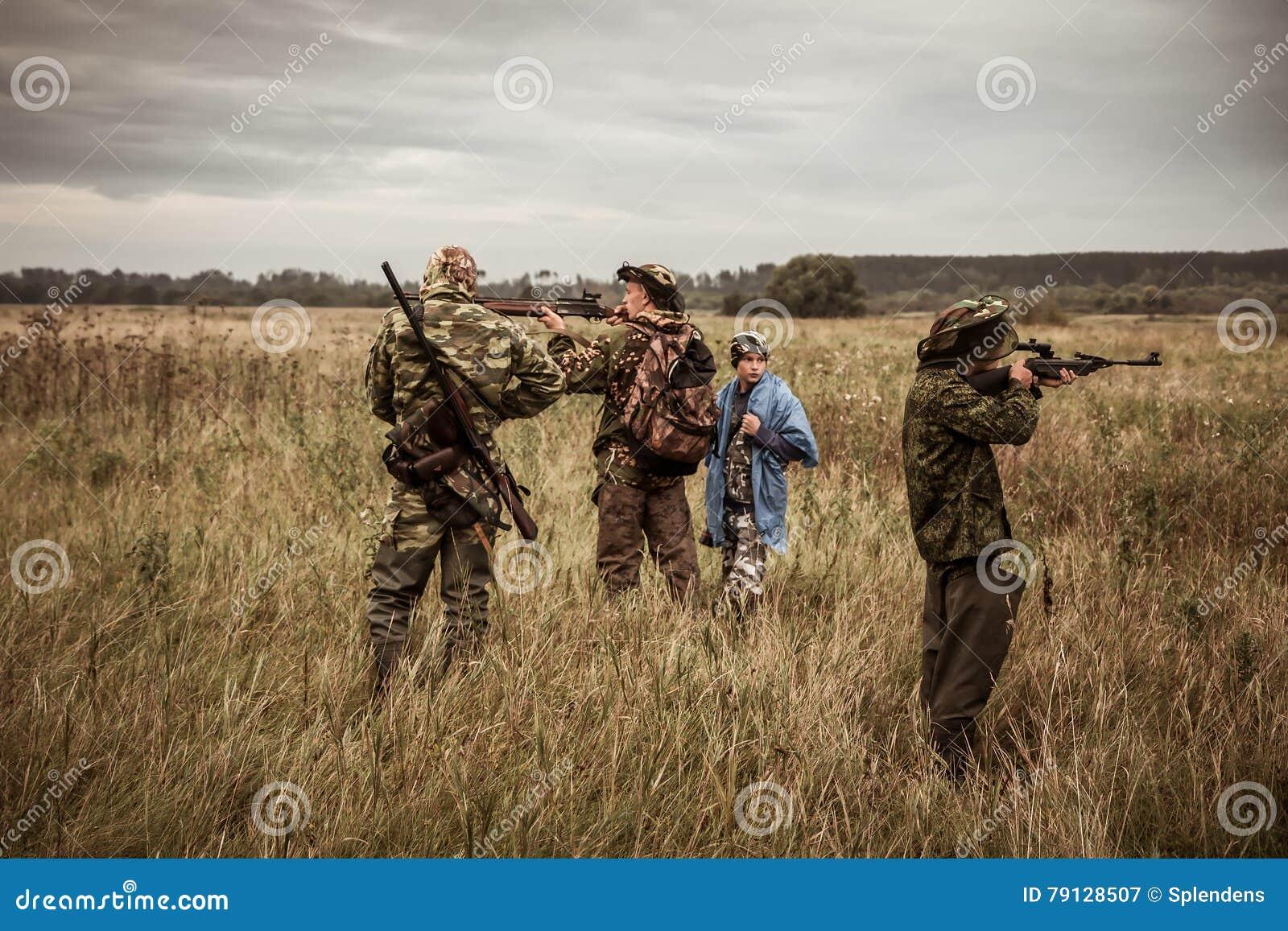 Scène de chasse avec des chasseurs visant pendant la saison de chasse dans le domaine rural dans le jour obscurci avec le ciel dé