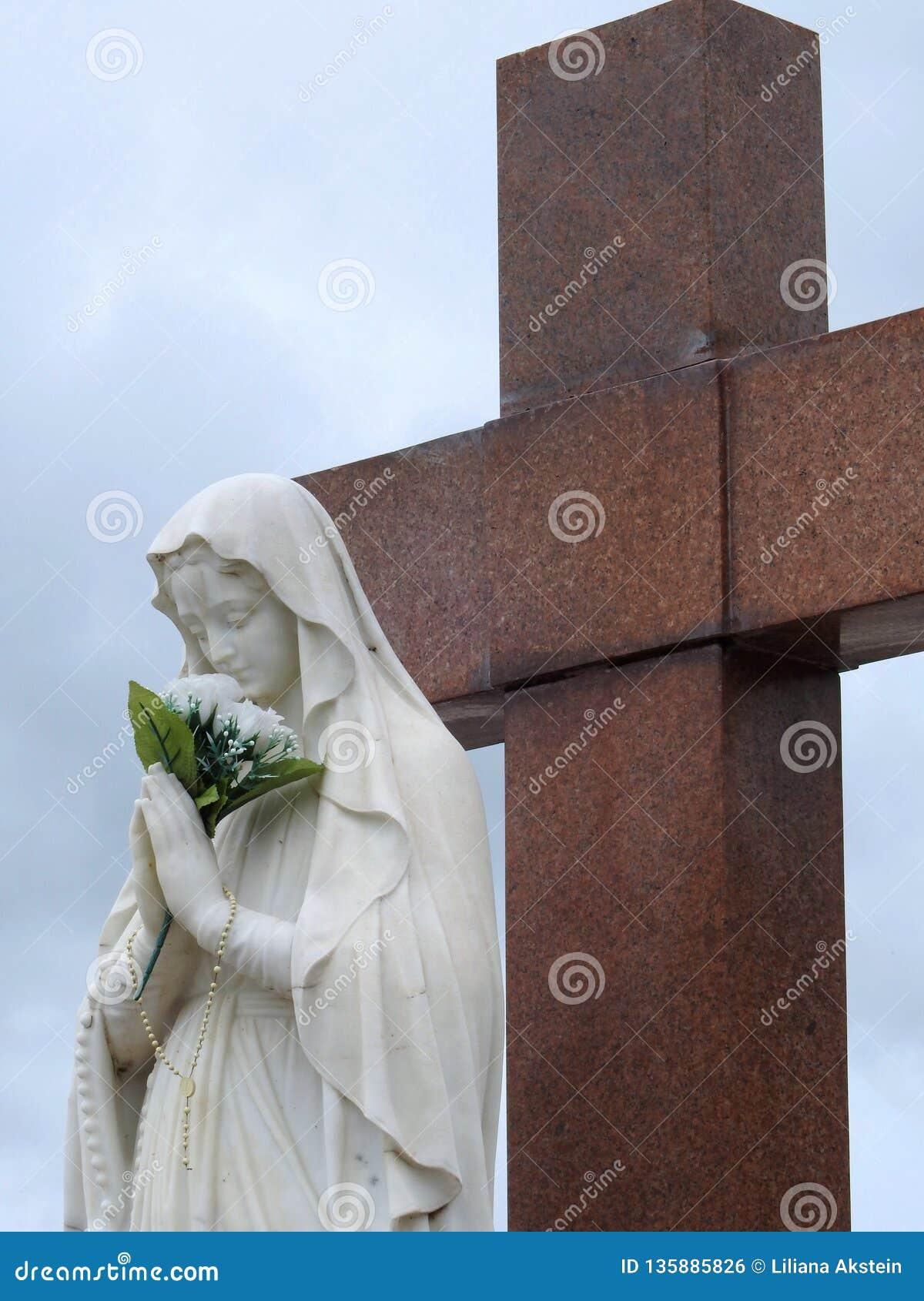 Scène in een begraafplaats: standbeeld van Maagdelijke Mary die een boeket van witte bloemen voor een groot granietkruis houden