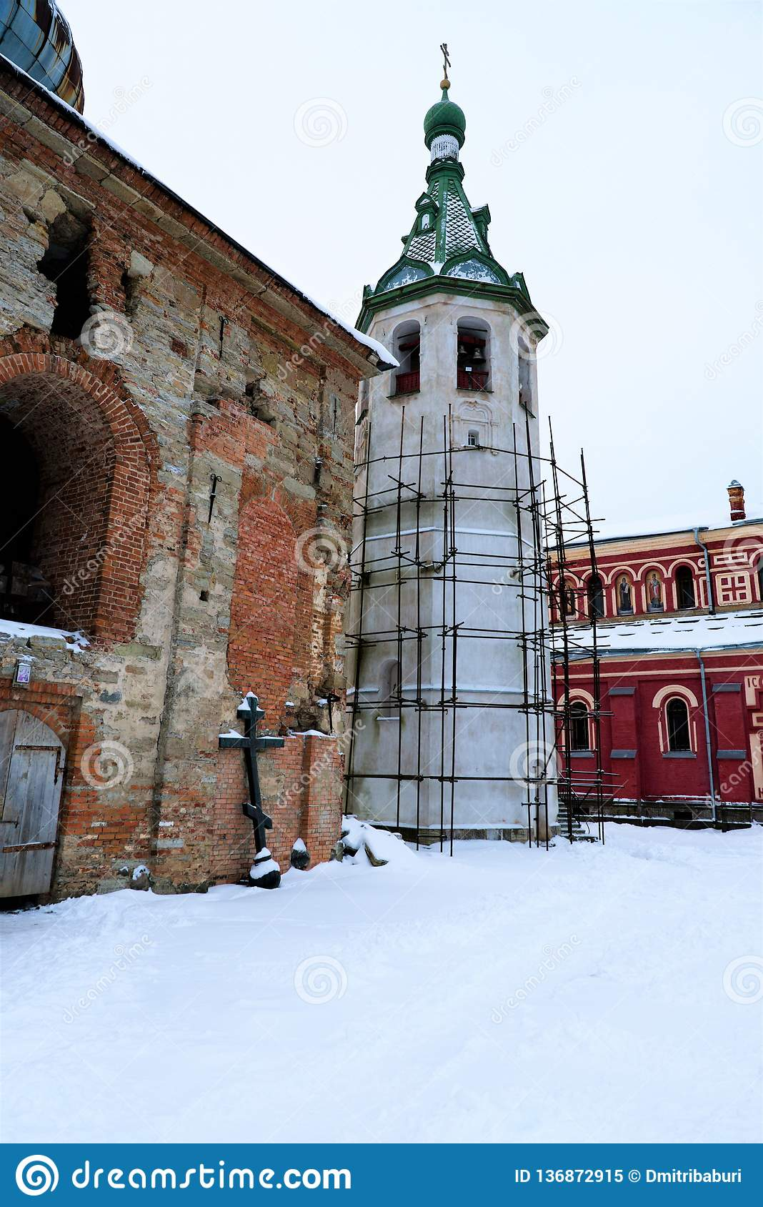 Scaffolding on the restored bell tower and a half-destroyed chapel in Nikolsky male monastery, Russia.