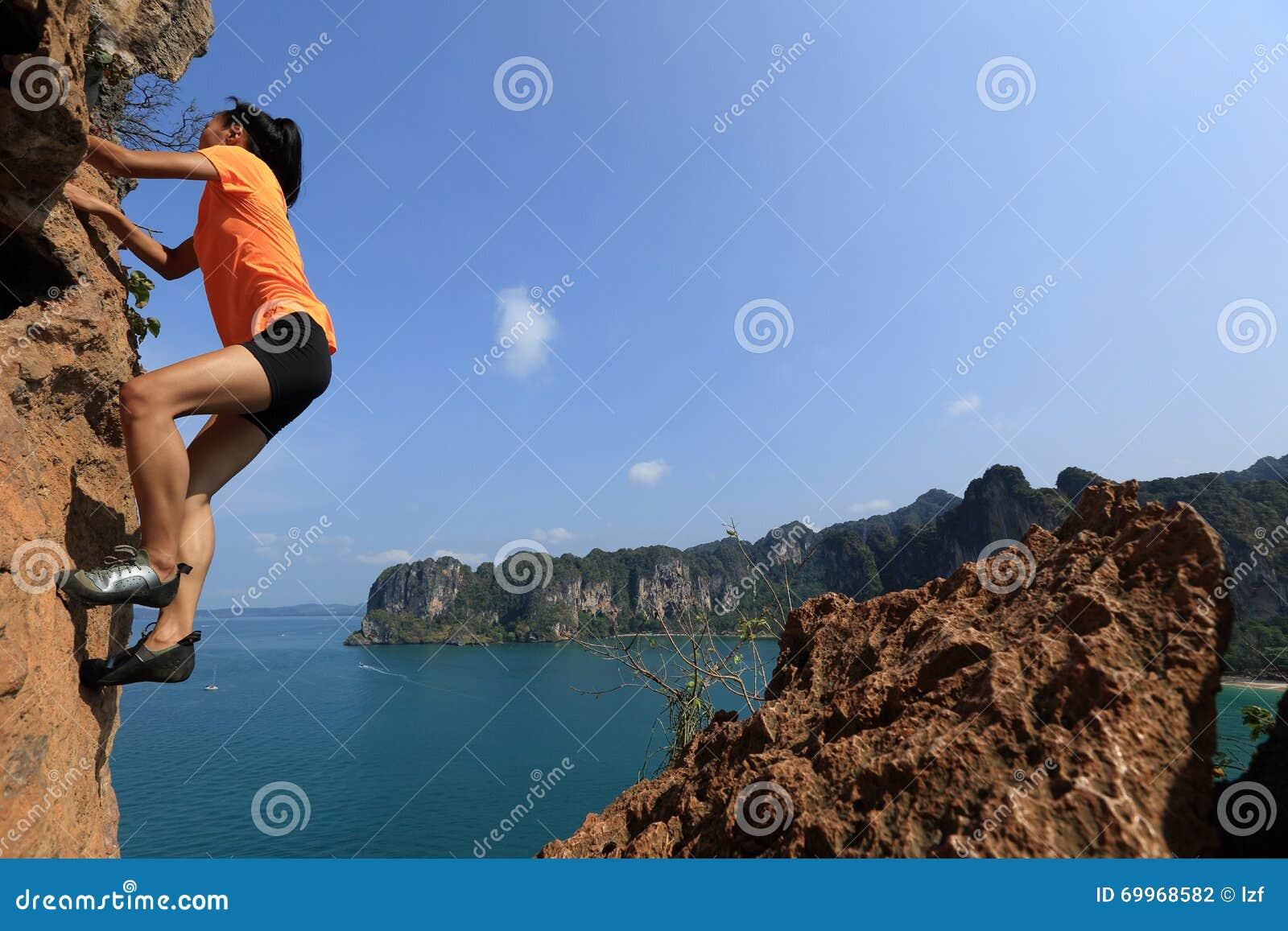 Scalatore della donna che scala alla roccia della montagna - Alla colorazione della spiaggia ...