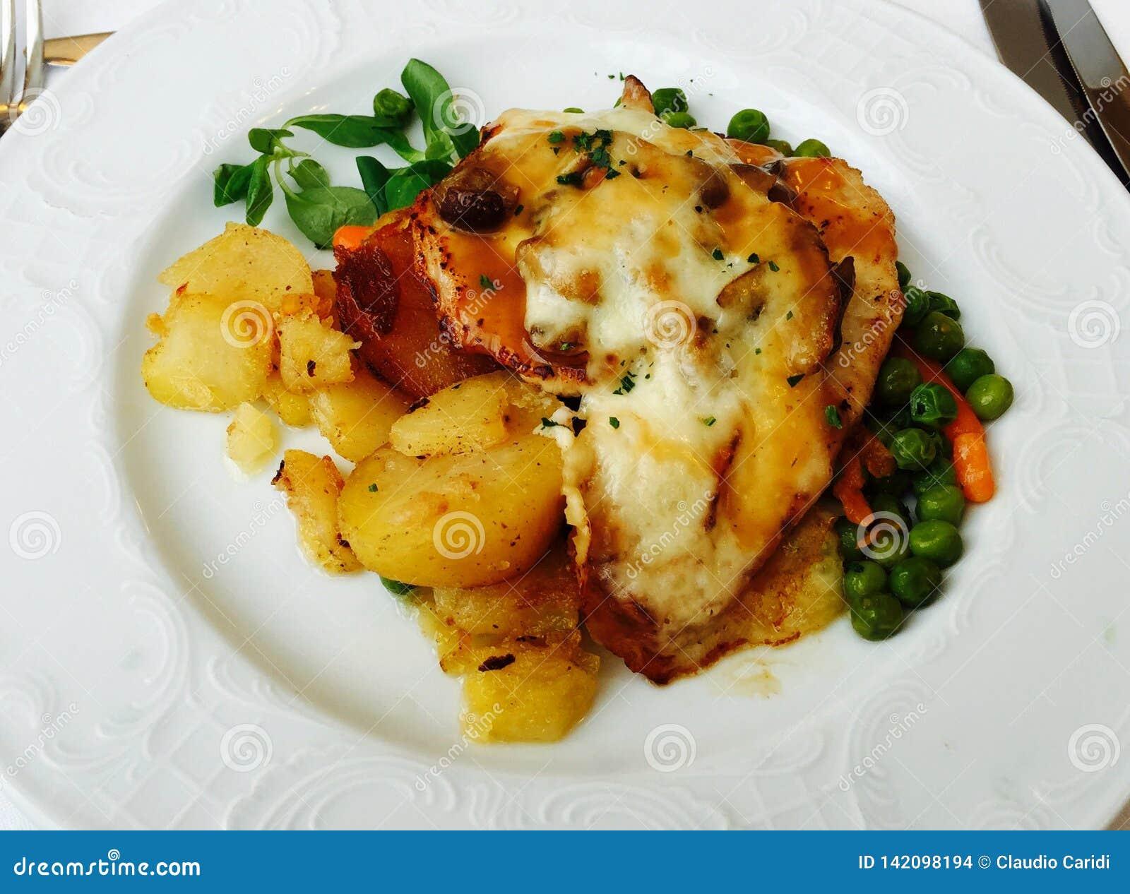 Scaloppina con il prosciutto e formaggio, patate, carote e piselli