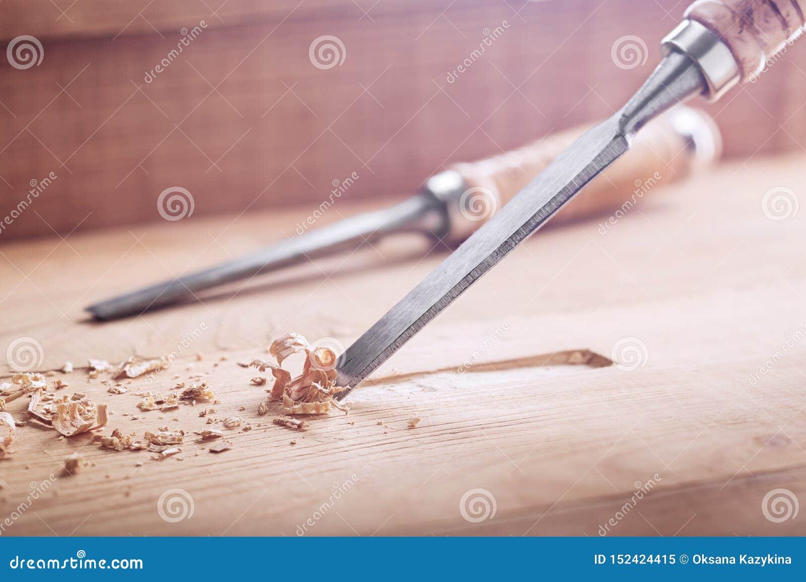 Scalpello da legno che taglia scanalatura nella vecchia plancia del pino per la serratura di porta