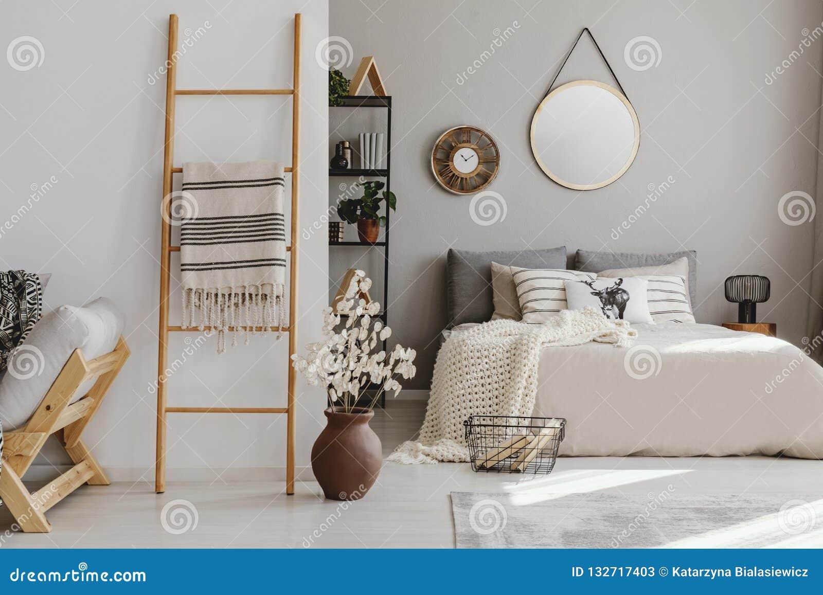 Scandi otwartej przestrzeni sypialni wnętrze z łóżkiem z dzianiną powszechna, wiele poduszki, stojak z książkami i wystrój, dywan