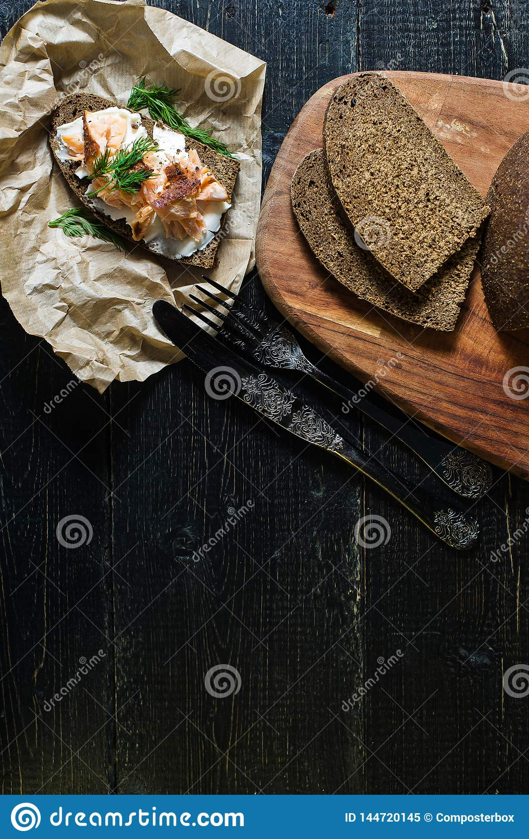 Scandinavian sandwich with smoked salmon fillet on black bread with soft cheese