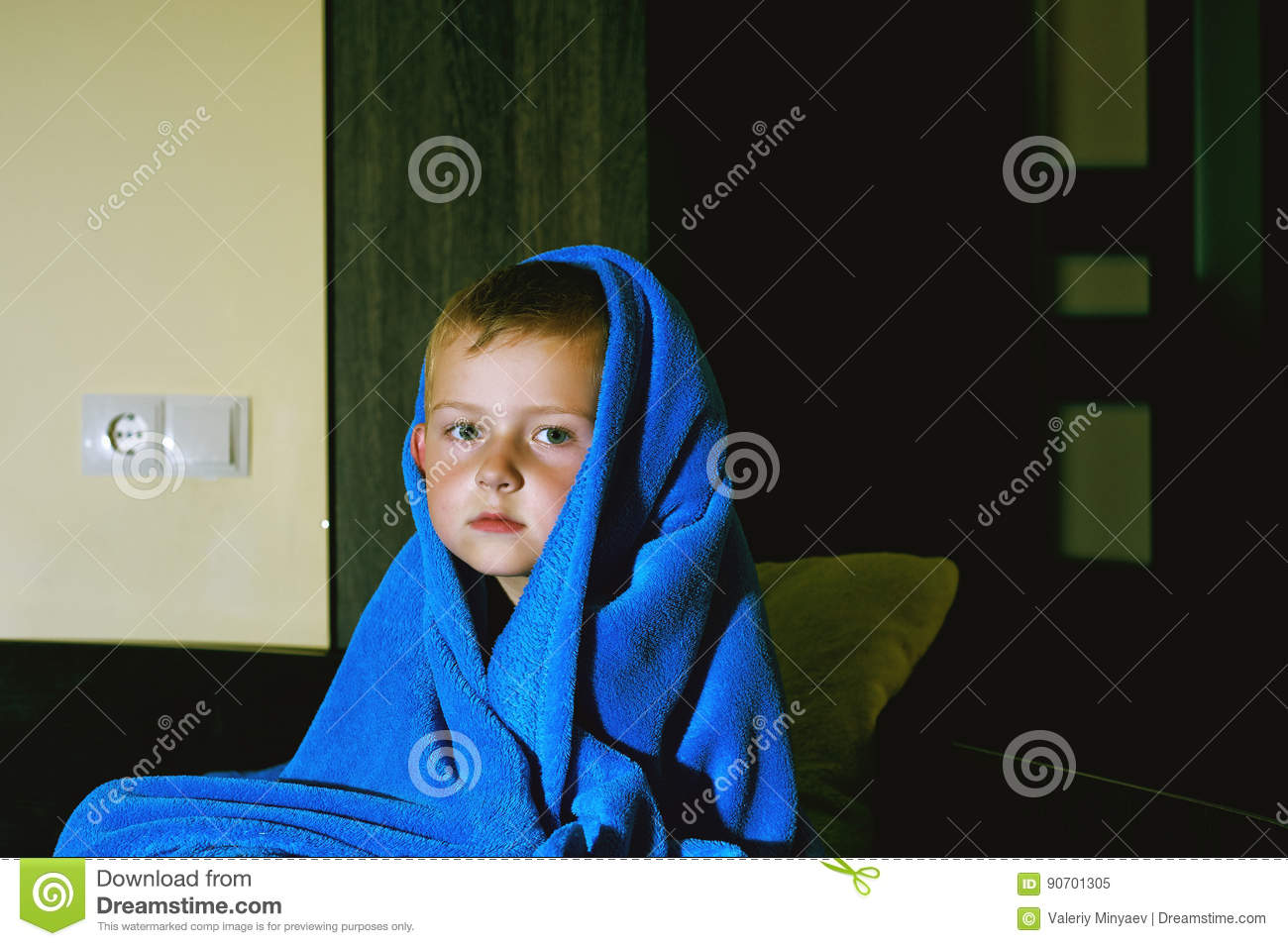 A scared boy in bed at night . Children`s fears