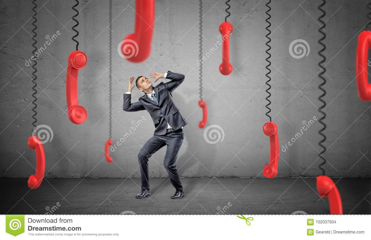 A scared businessman on concrete background hides from many red retro phone receivers hanging down on their cords.
