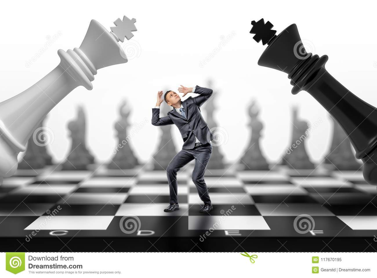 A scared businessman stands between a black and a white chess kings falling on him.