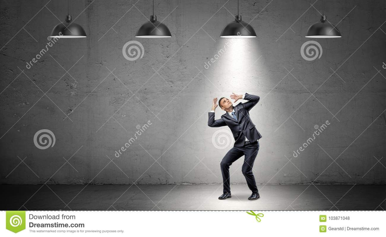 A scared businessman stands cowering under the rays of industrial pendant lights right above him.
