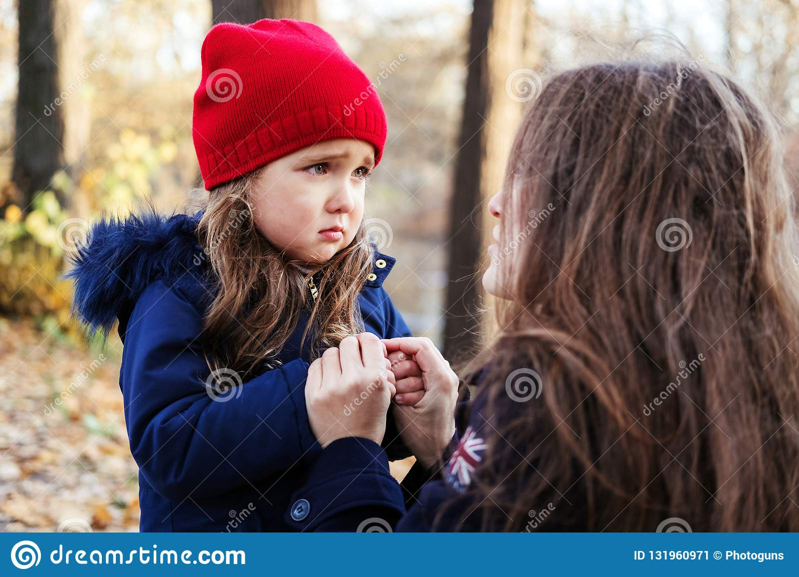 Scared daughter holding mother`s hands in autumn park