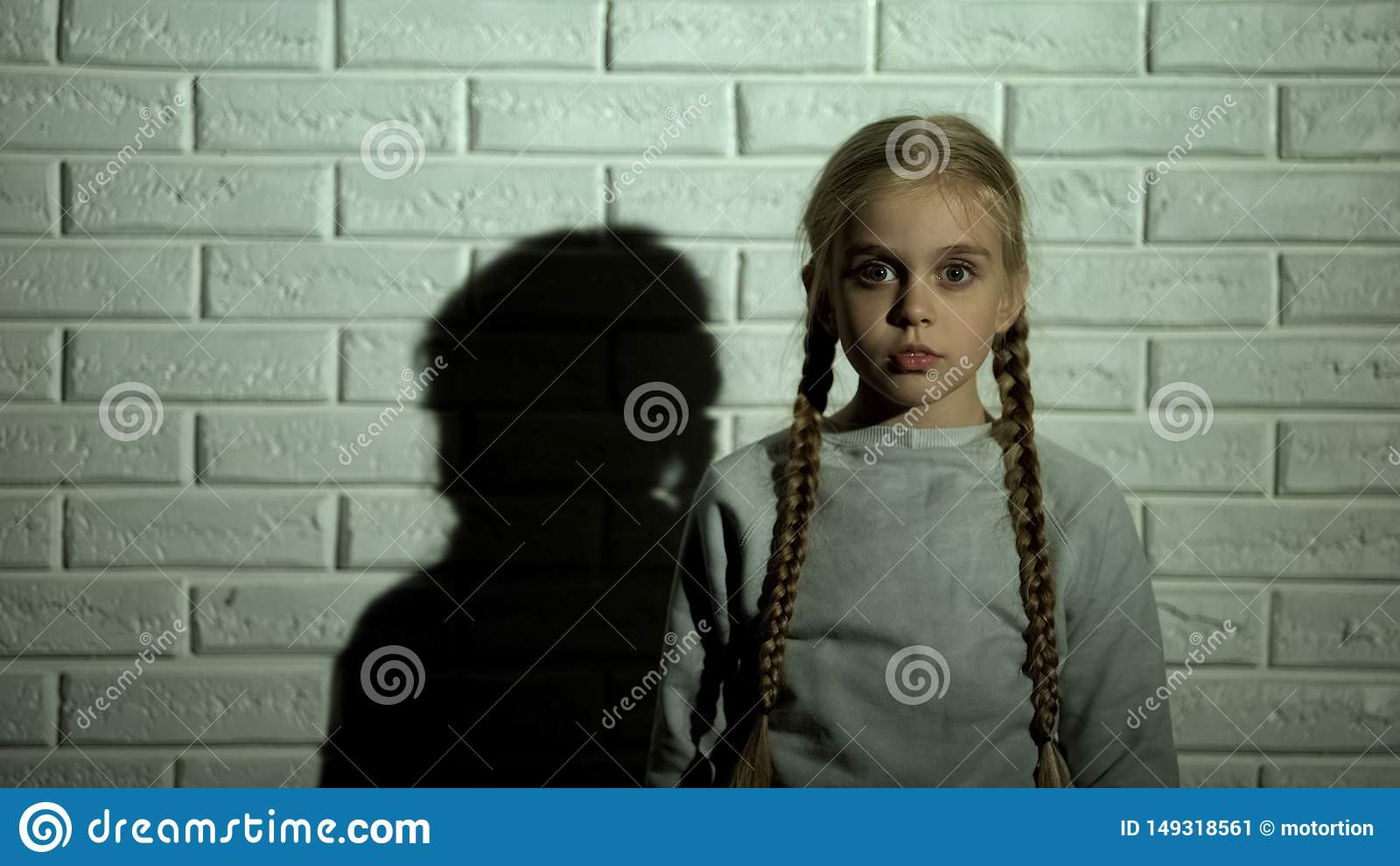 Scared female kid looking at camera, childish phobia, fear and horror concept