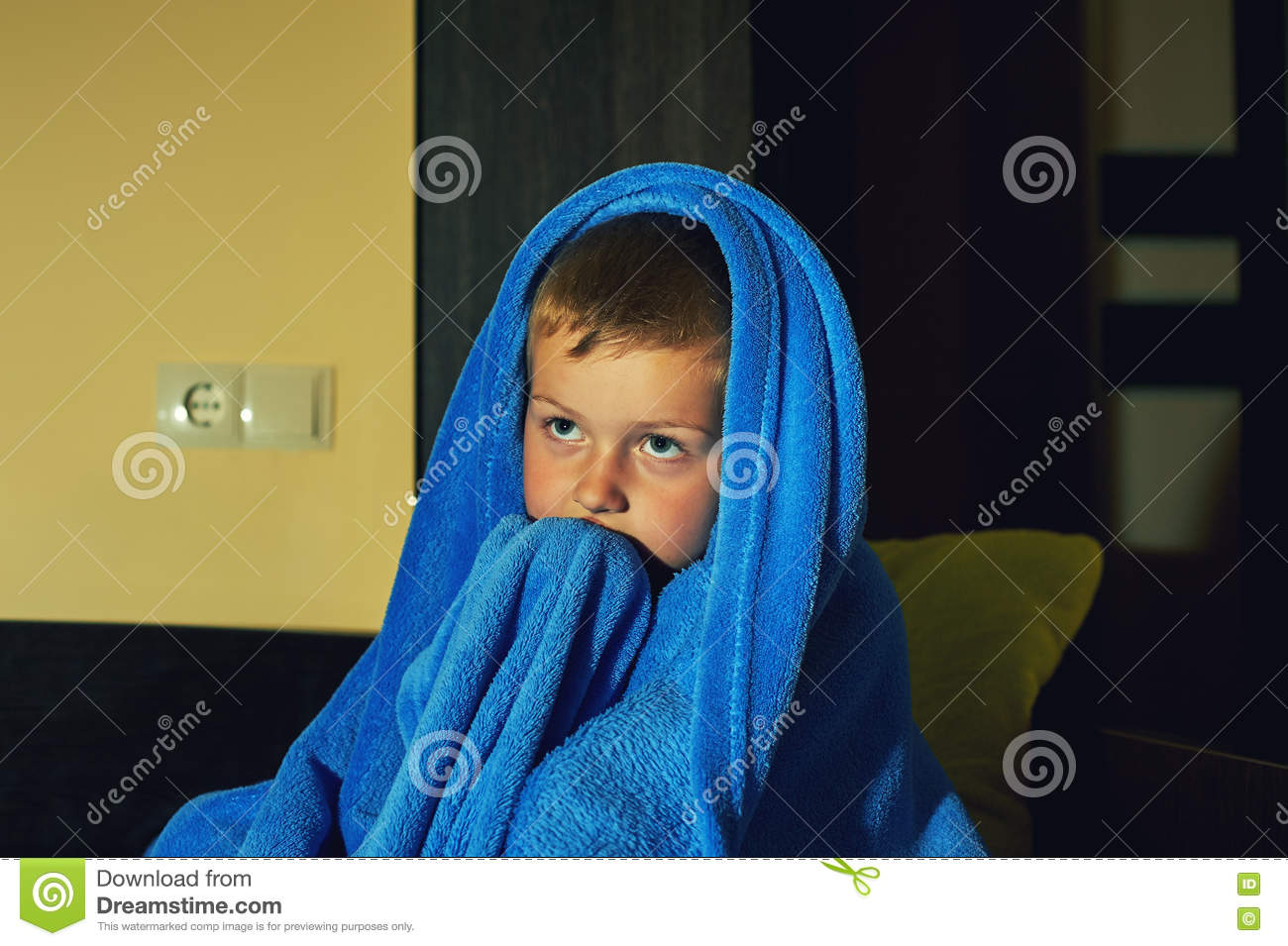 A scared little boy afraid in bed at night , childhood fears