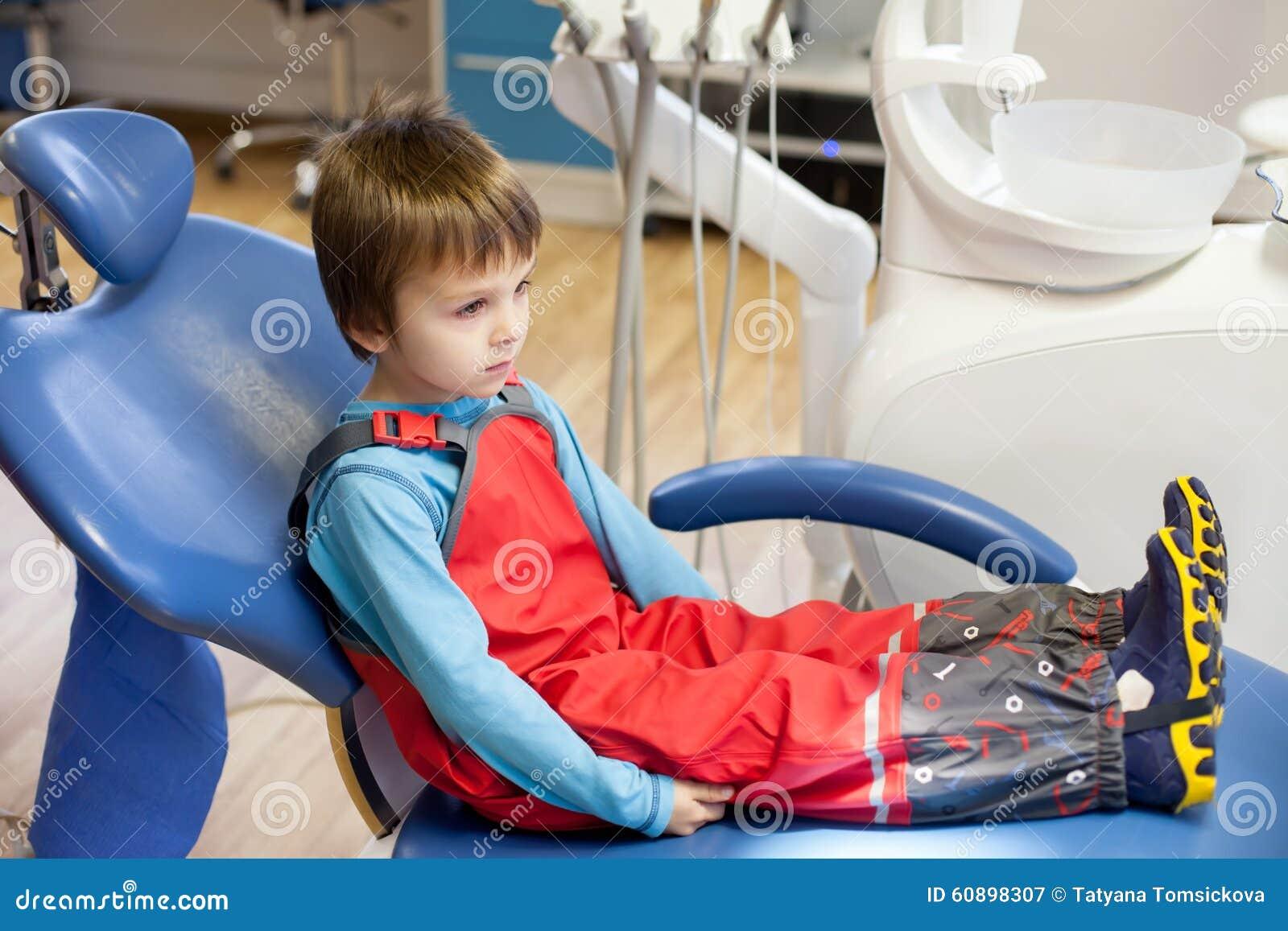 Scared Little Child Boy Sitting On Dentist Chair