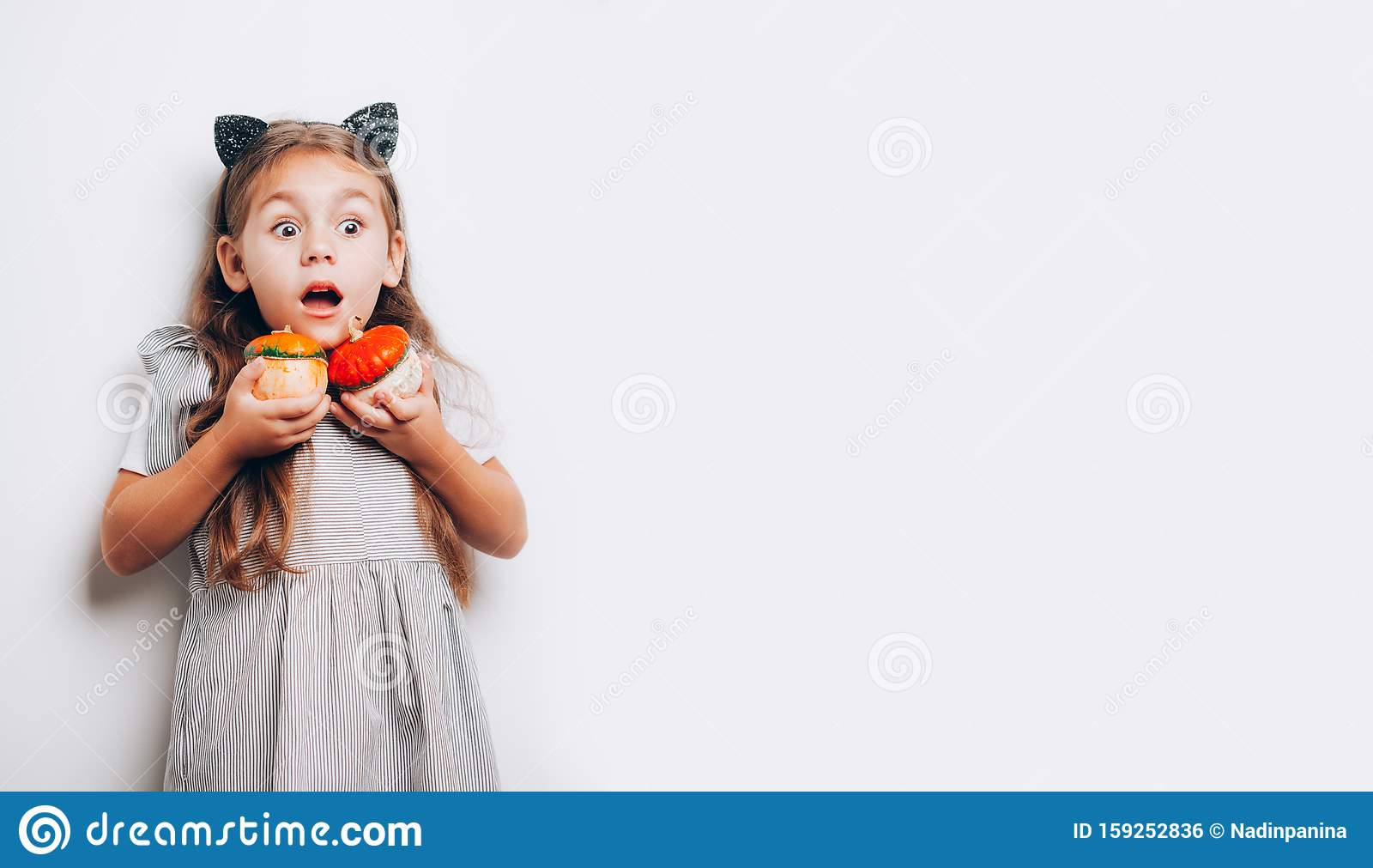 Scared little girl holding decorative pumpkins on white background