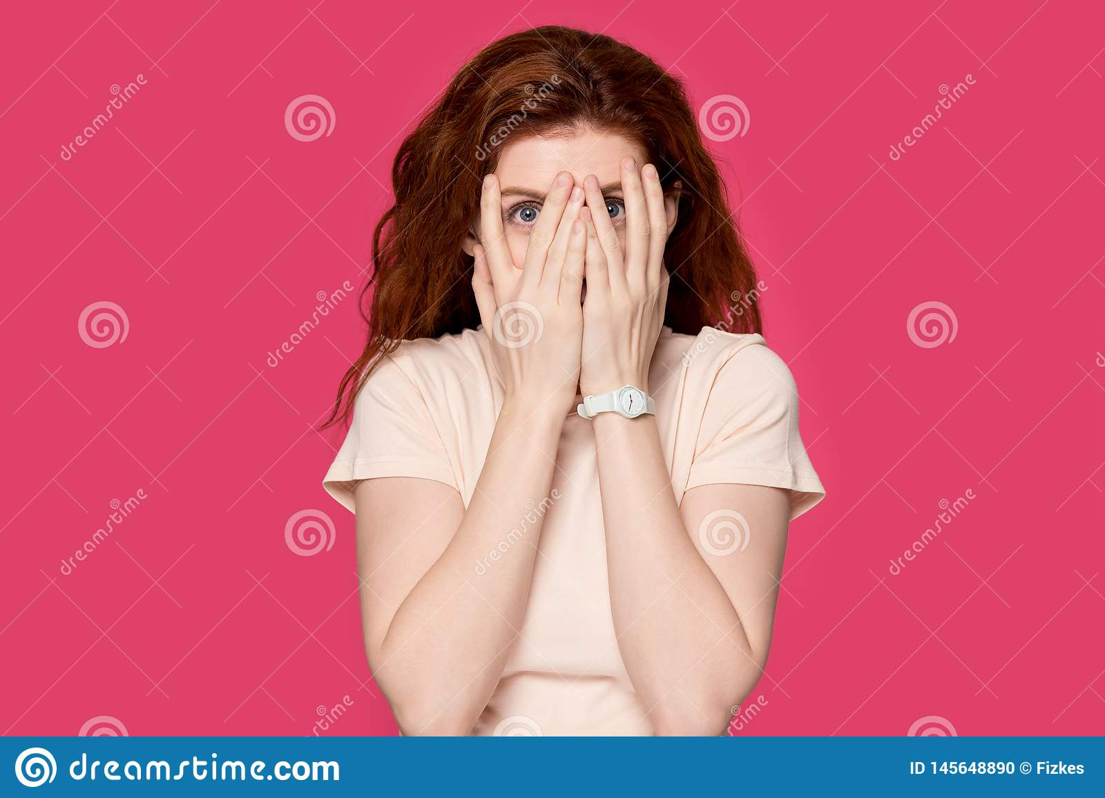 Scared redhead girl cover face peeking through fingers