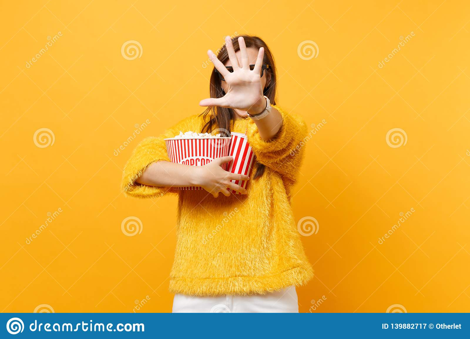 Scared woman in 3d imax glasses closing screen by hand, watching movie film, holding popcorn, plastic cup of cola or