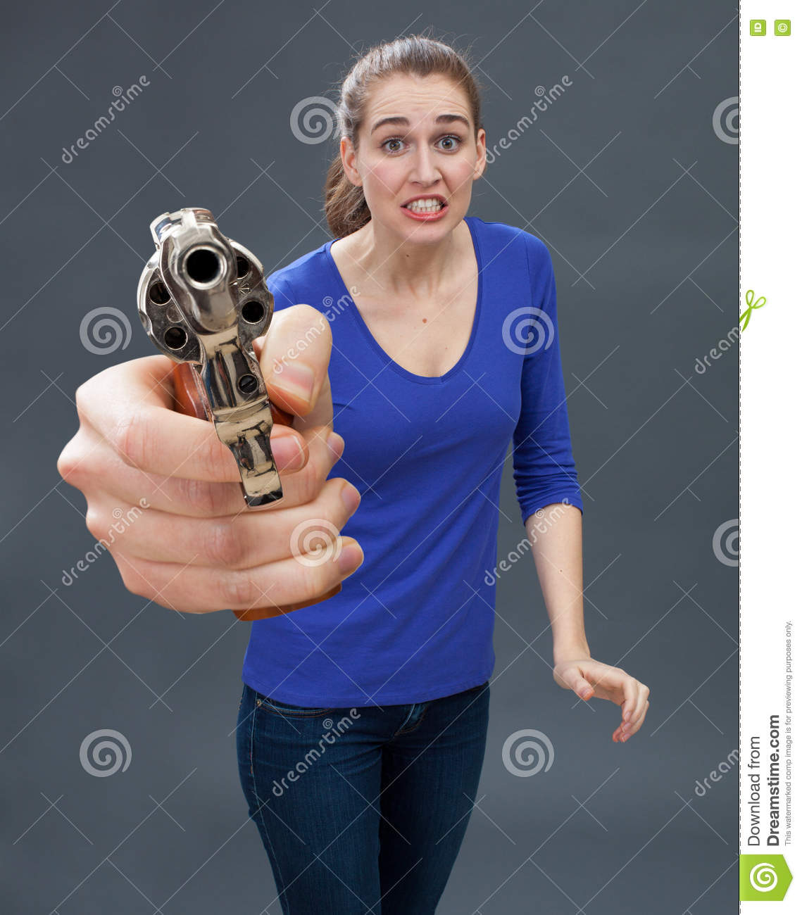 Scared young woman with gun expressing anxiety for self-defense
