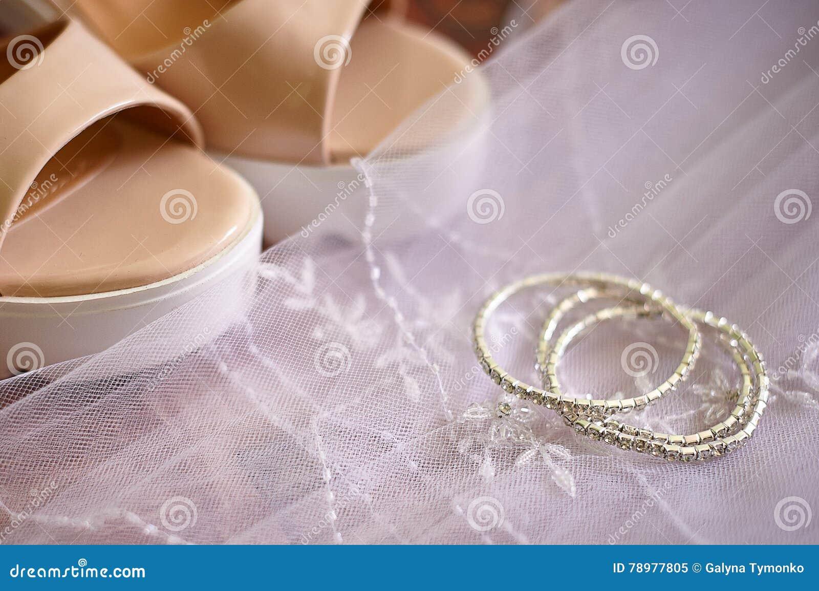 Scarpe della sposa ed accessori di nozze su fondo di un velo