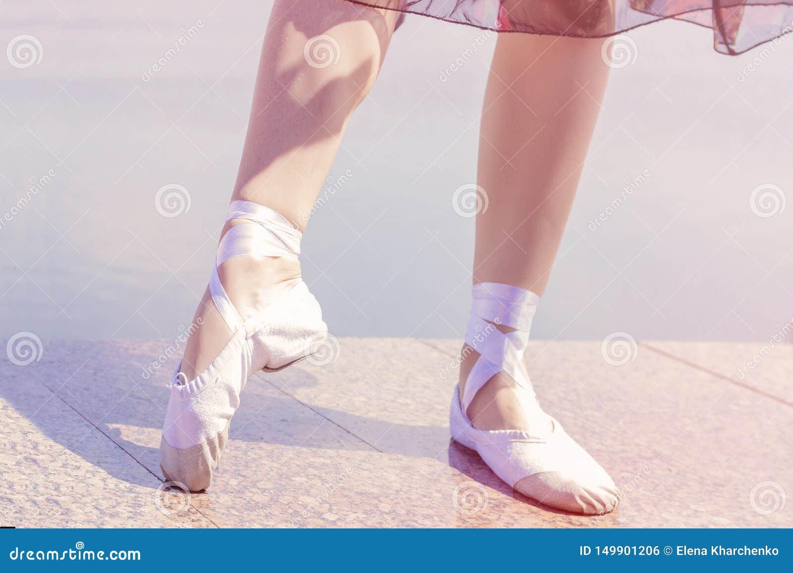 Scarpe di balletto per ballare calzate sulle loro ragazze del ballerino dei piedi