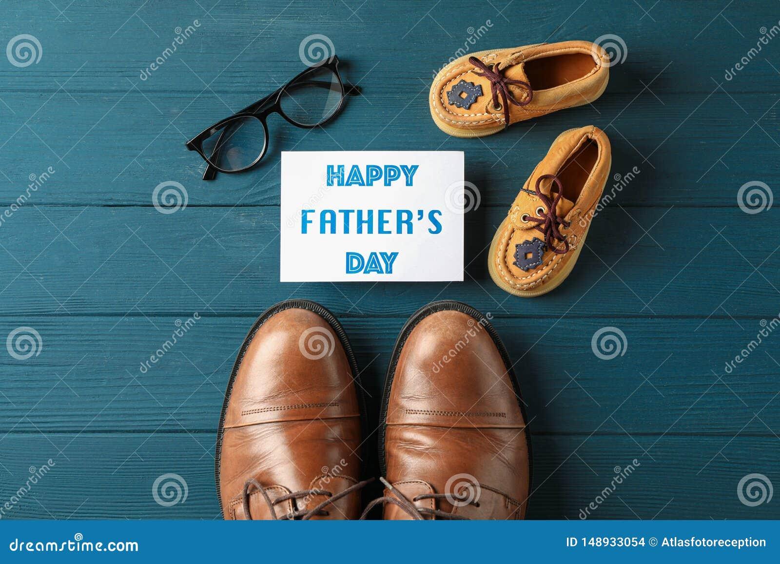 Scarpe di cuoio di Brown, le scarpe dei bambini, giorno di padri felice dell iscrizione e vetri su fondo di legno