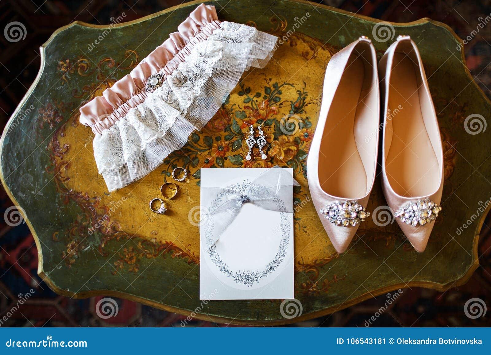 Scarpe di nozze sulla tavola d annata, sulla giarrettiera nuziale e sugli anelli