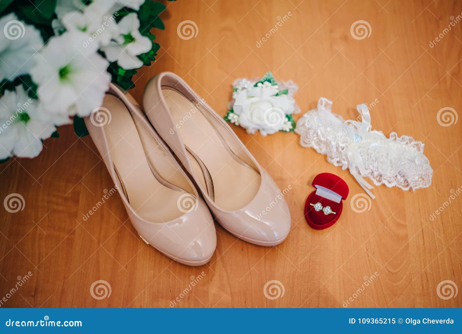 Scarpe, fedi nuziali e giarrettiera della sposa